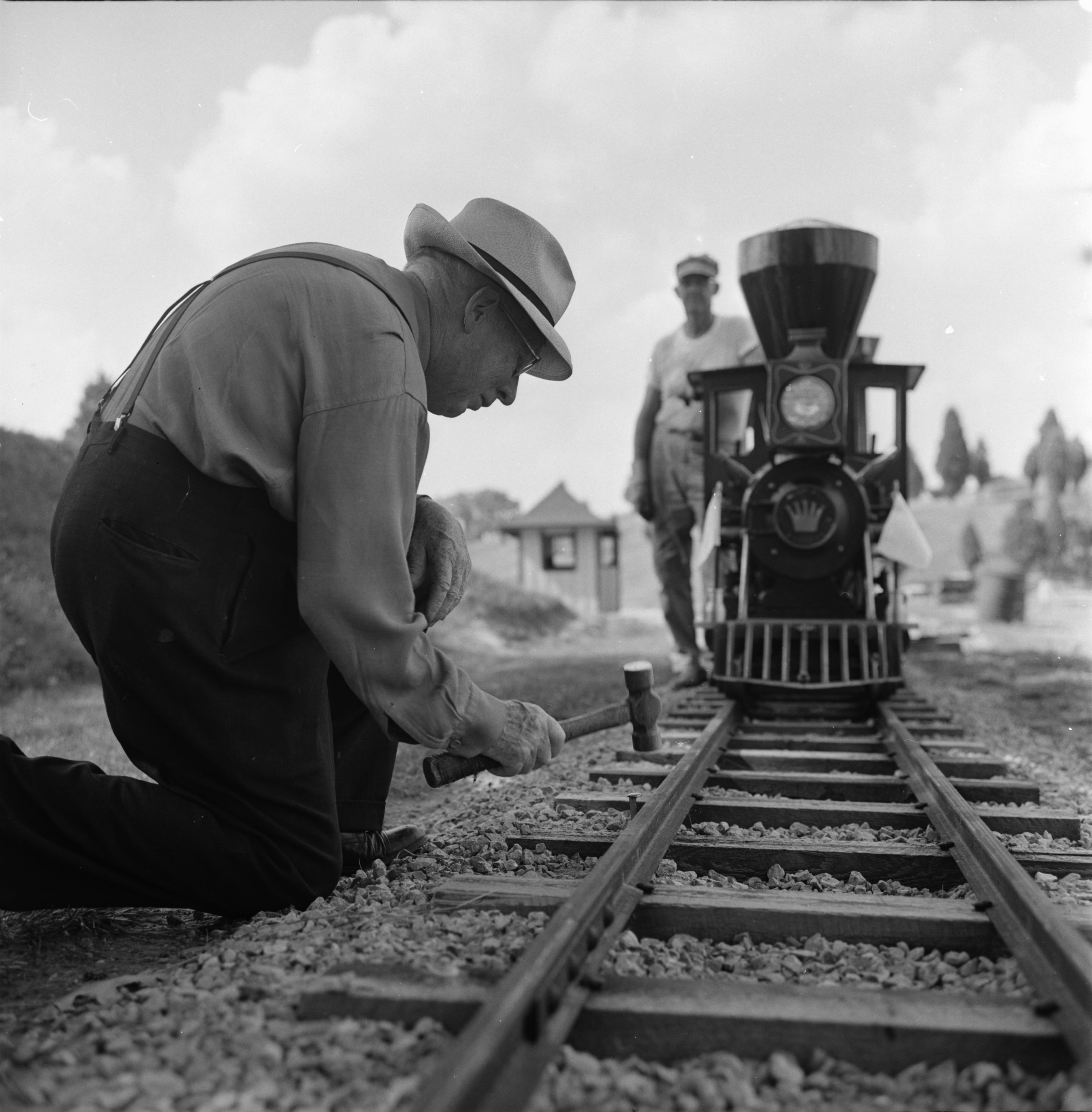 Man Hammering Nail Into Donald Drew's Miniature Railroad