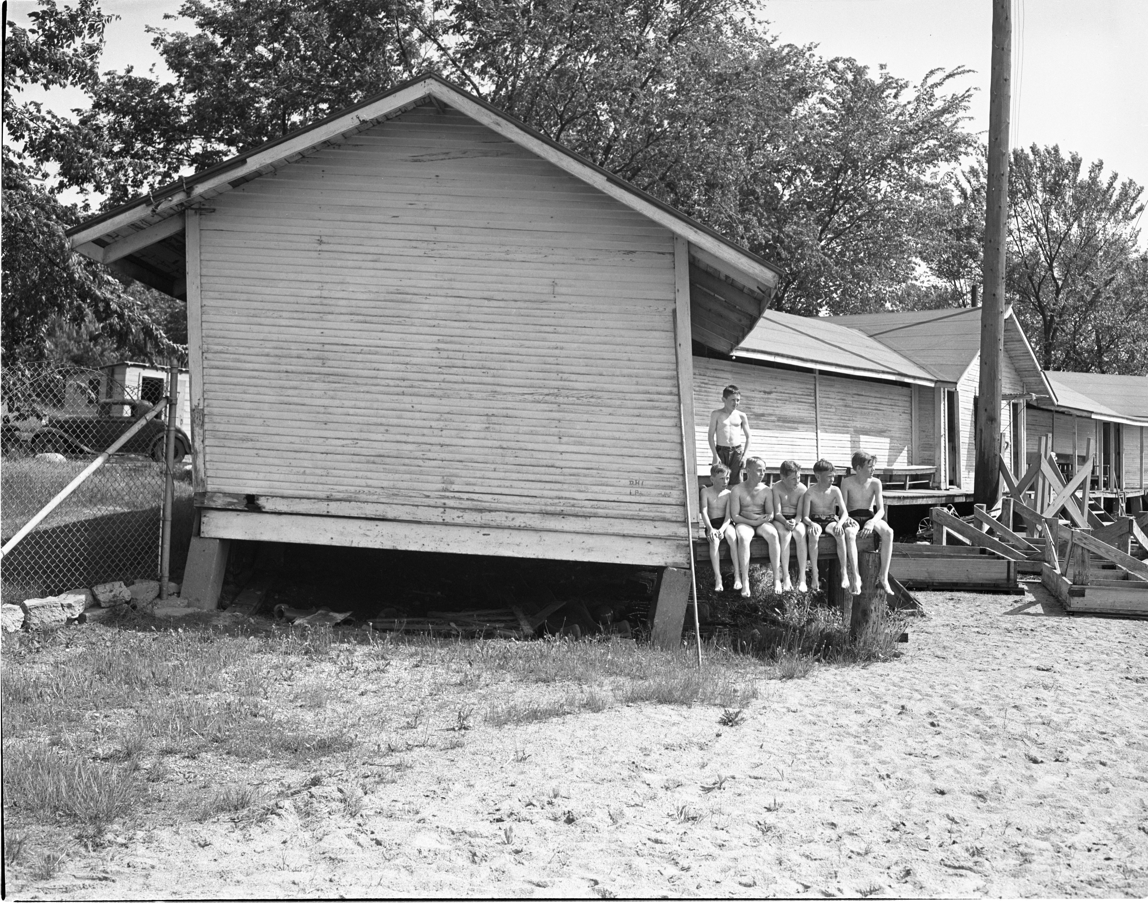 Young Swimmers Relax Outside The Dilapidated Bathhouse At Ann Arbor Municipal Beach, June 1940 image