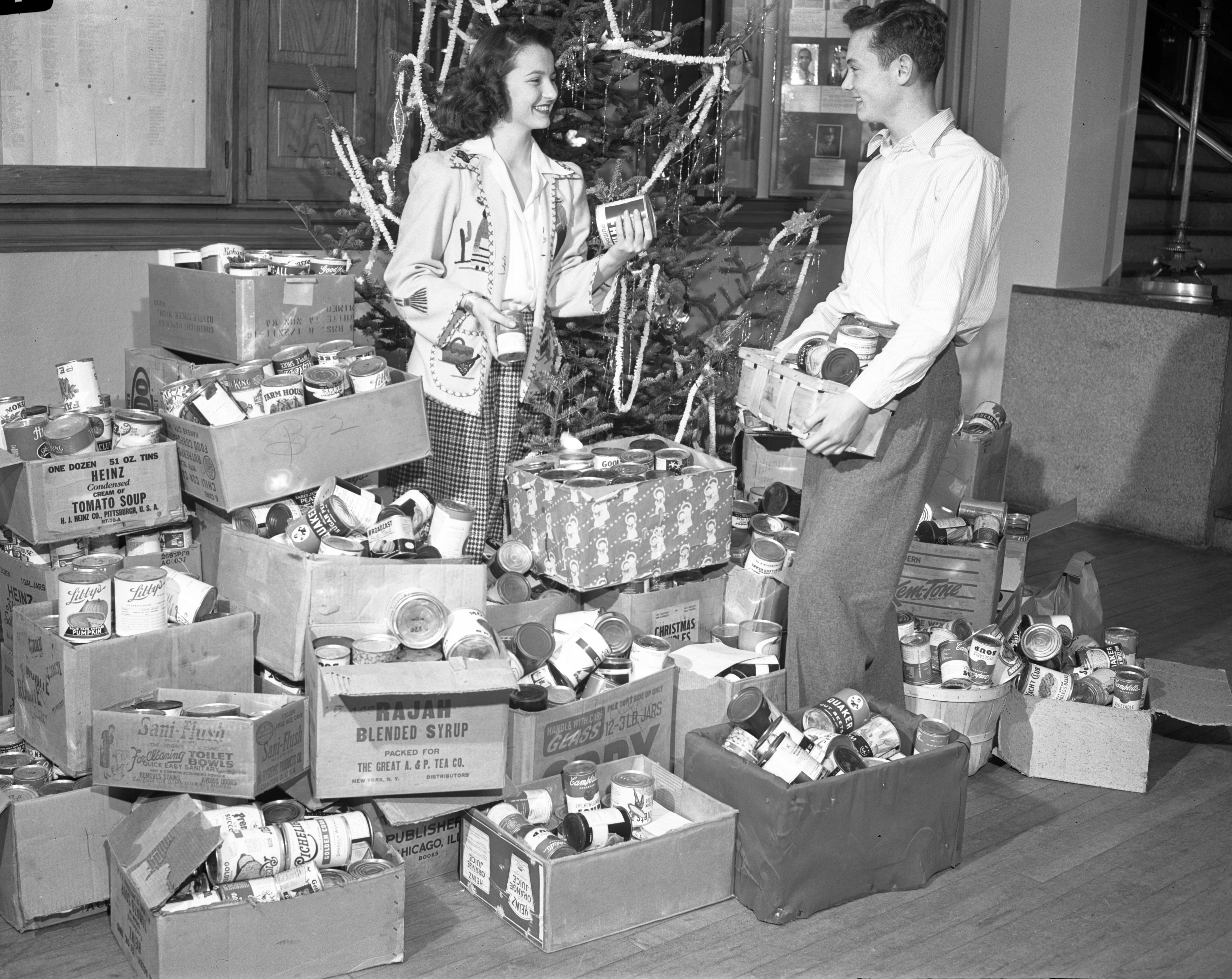 Ann Arbor High School students Catherine Warren and David West gather canned goods for needy, December 1945 image