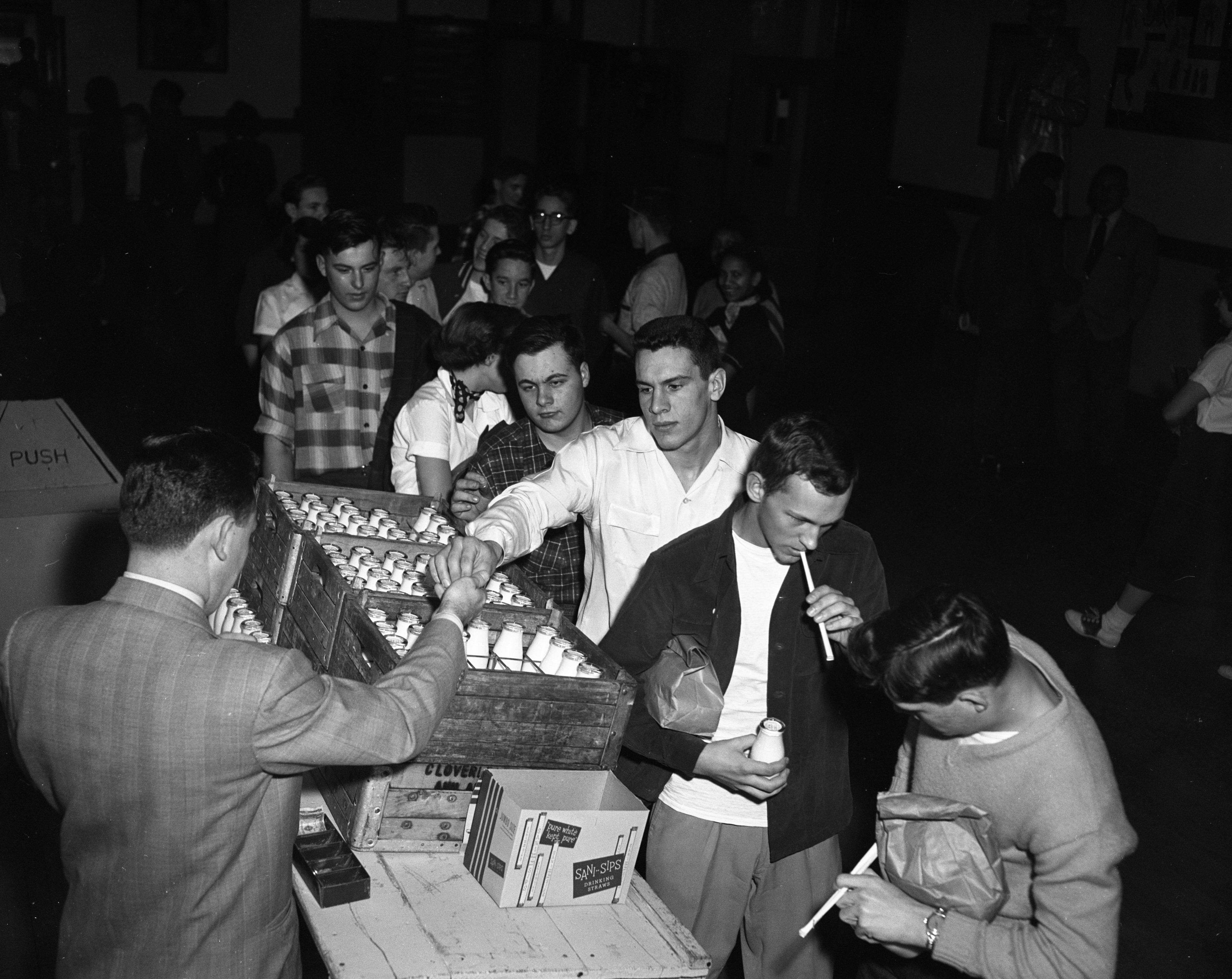 Thad Carr, administrative assistant at Ann Arbor High School, sells milk to students during lunch, February 1953 image
