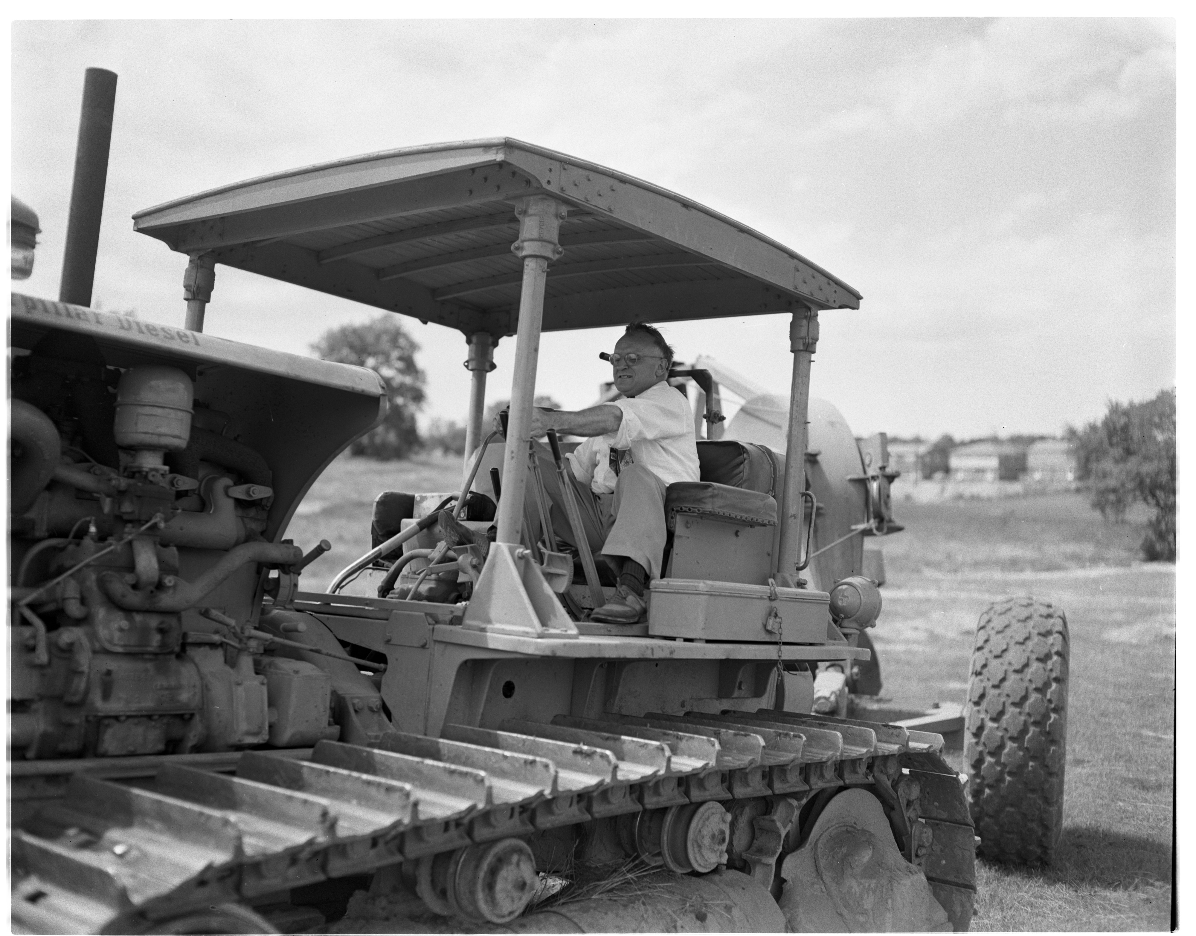 Trustee Ashley H. Clague Mans Steam Shovel at Groundbreaking Ceremony For New Ann Arbor High School, June 1953 image