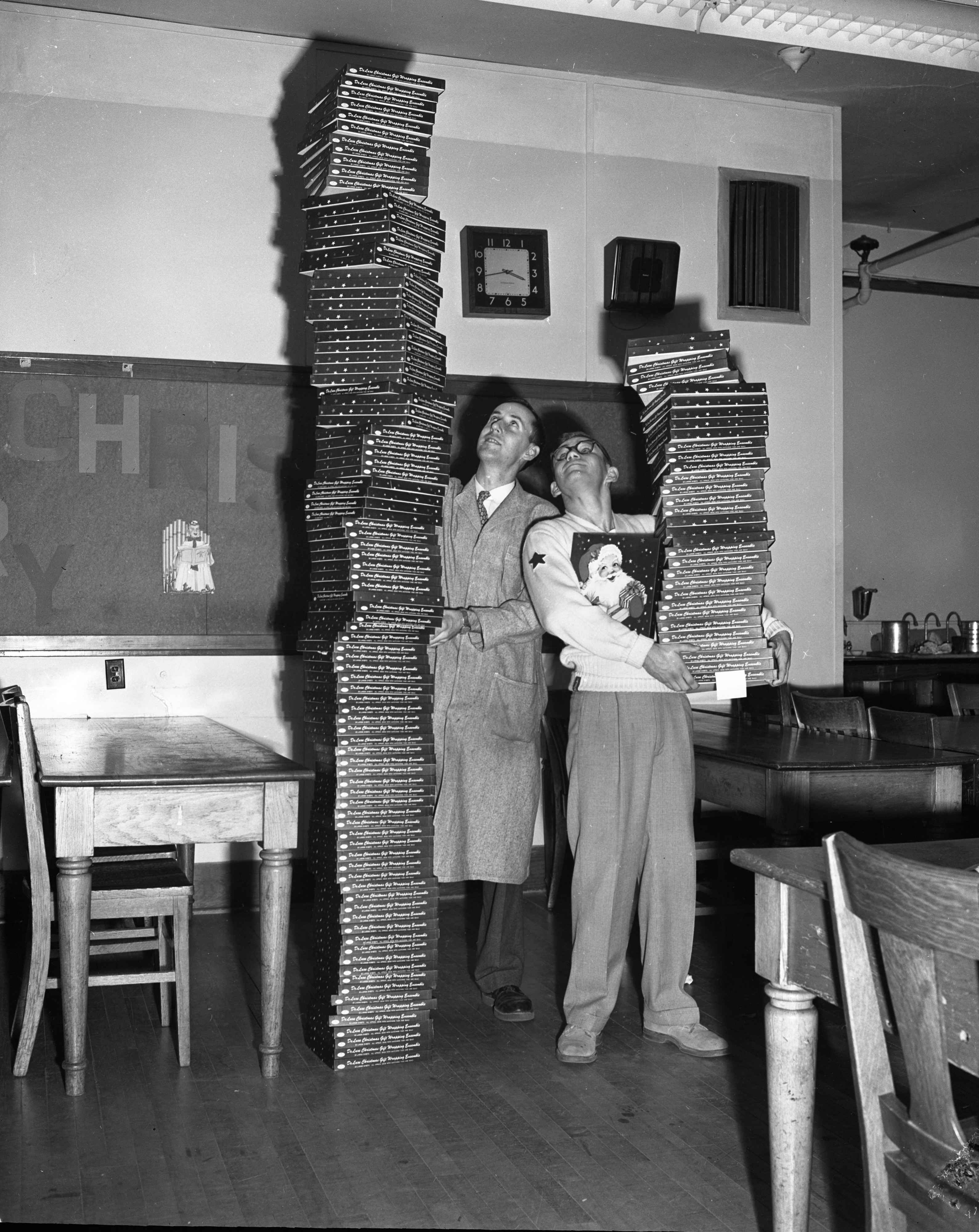 Ann Arbor High School teacher Albert Gallup helps student Chuck O'Hara hold up the 100 boxes of Christmas wrapping to sell, December 1954 image
