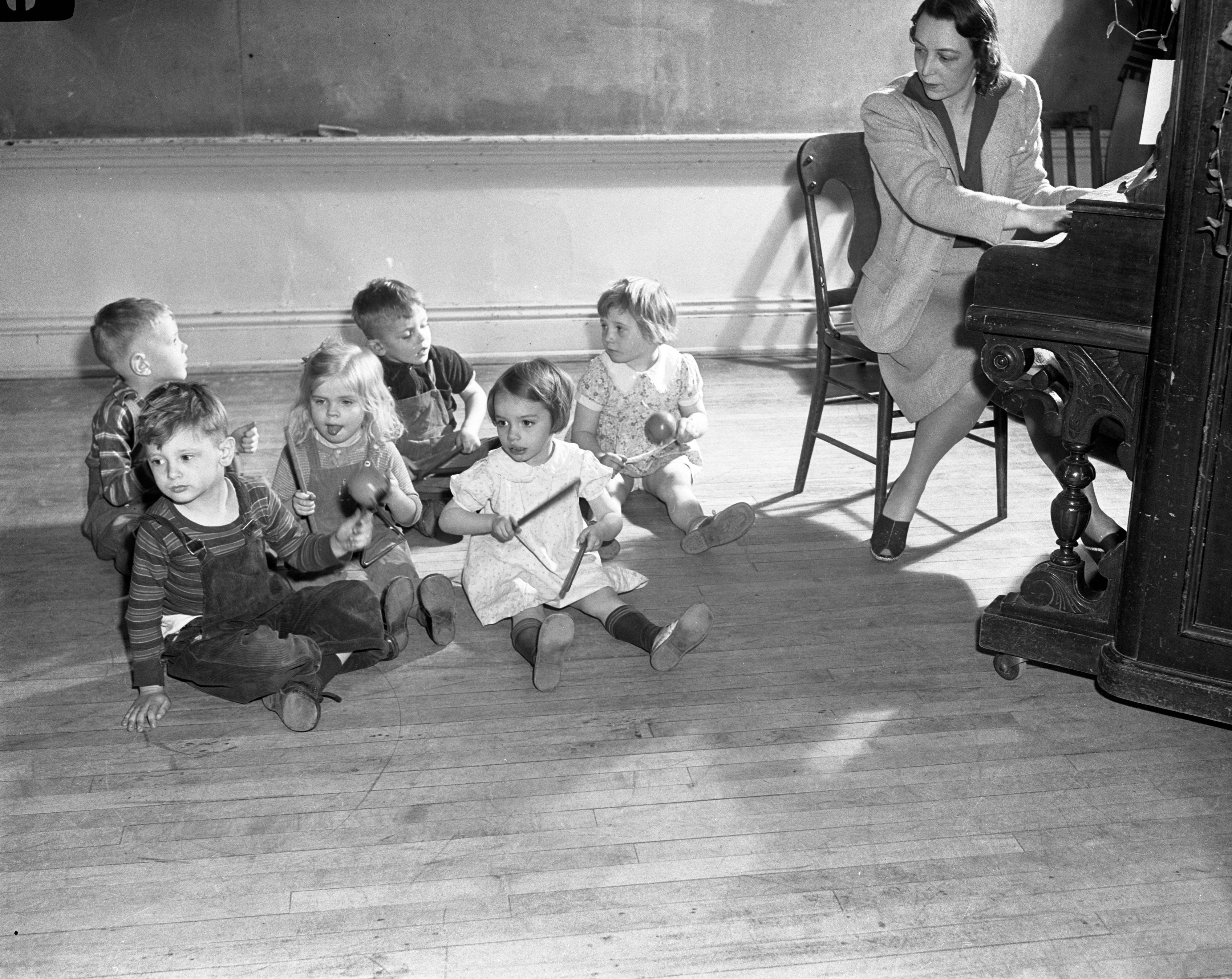 Mrs. Ken Dougherty teaches a rhythm class to defense Children at Perry School's Nursery, March 1942 image