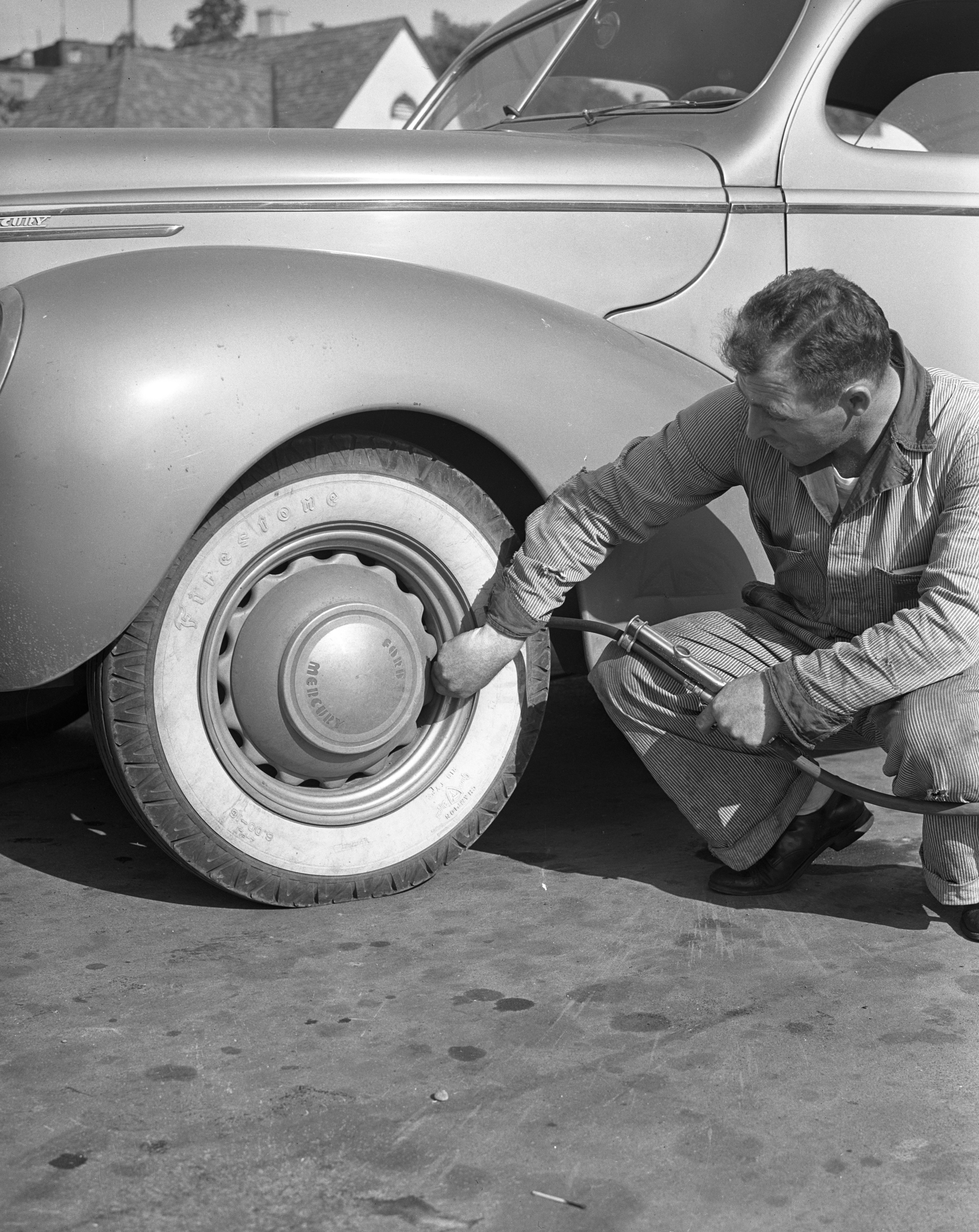 Bobby and the Old Professor: Man inflating a tire, July 1939 image