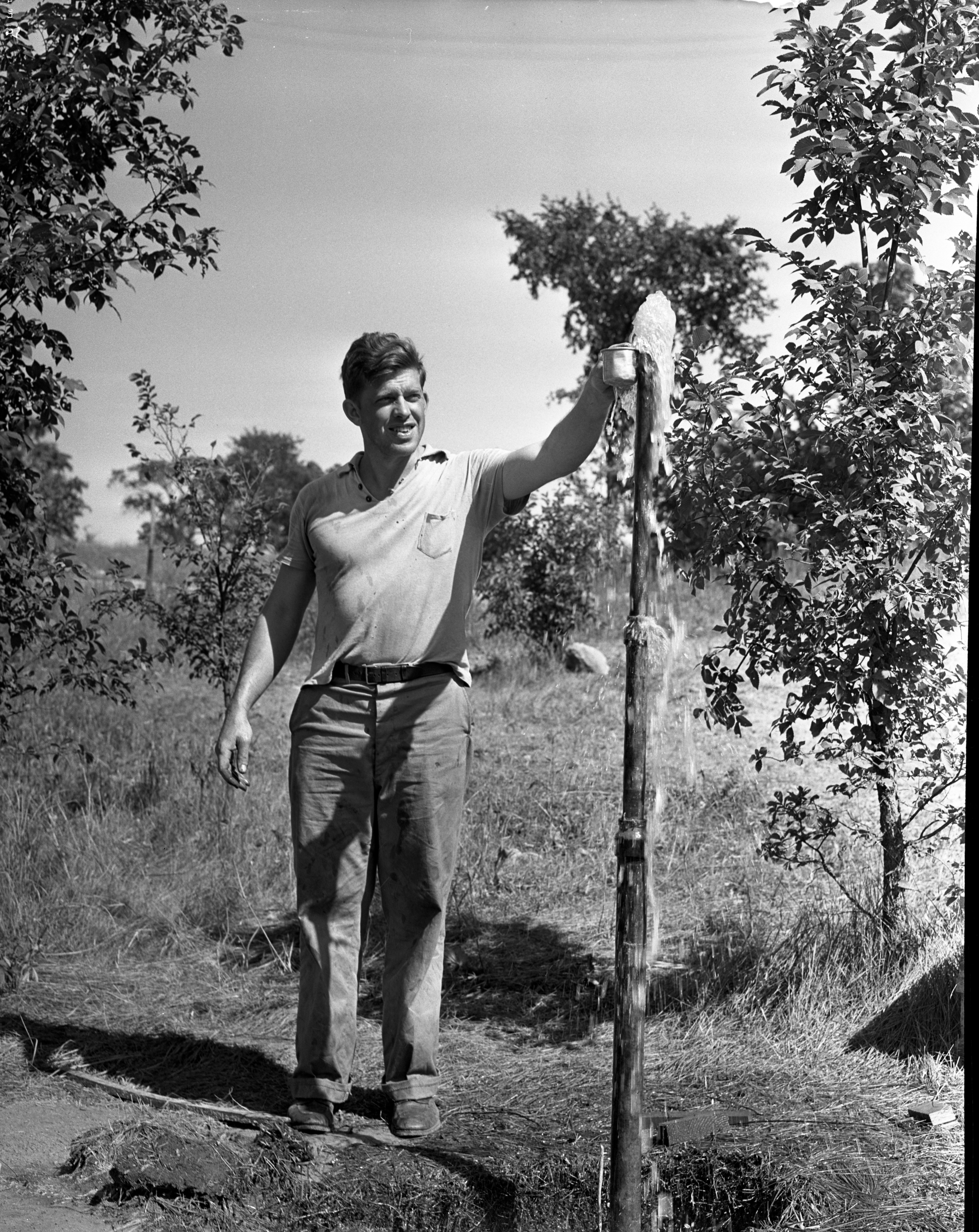 Joe Naggle stands next to an artesian well on Jackson Road, August 1939 image