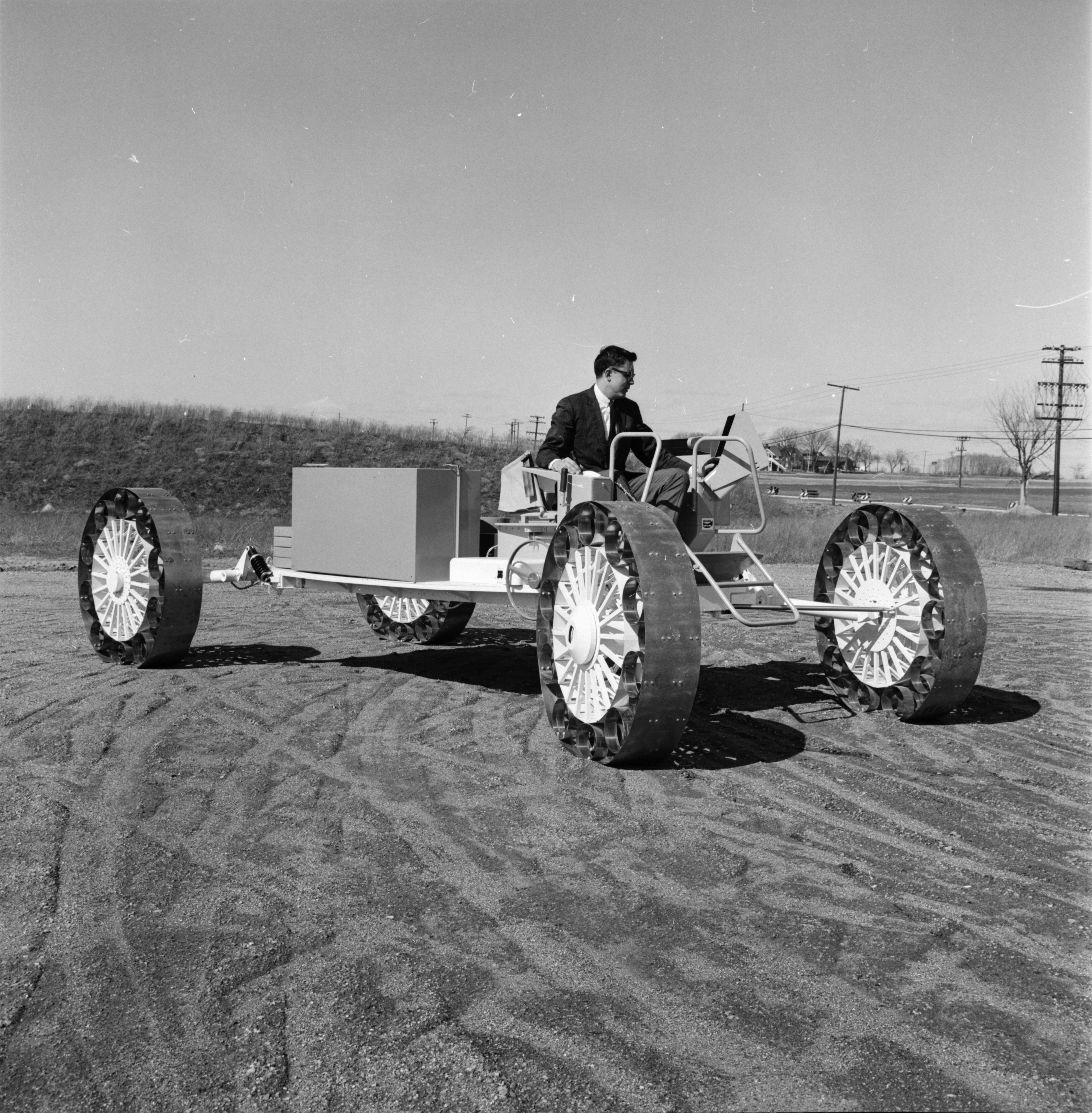 "Larry Ruble Of Bendix Corporation Drives ""Lunarmobile"" Moon Buggy, April 1967 image"