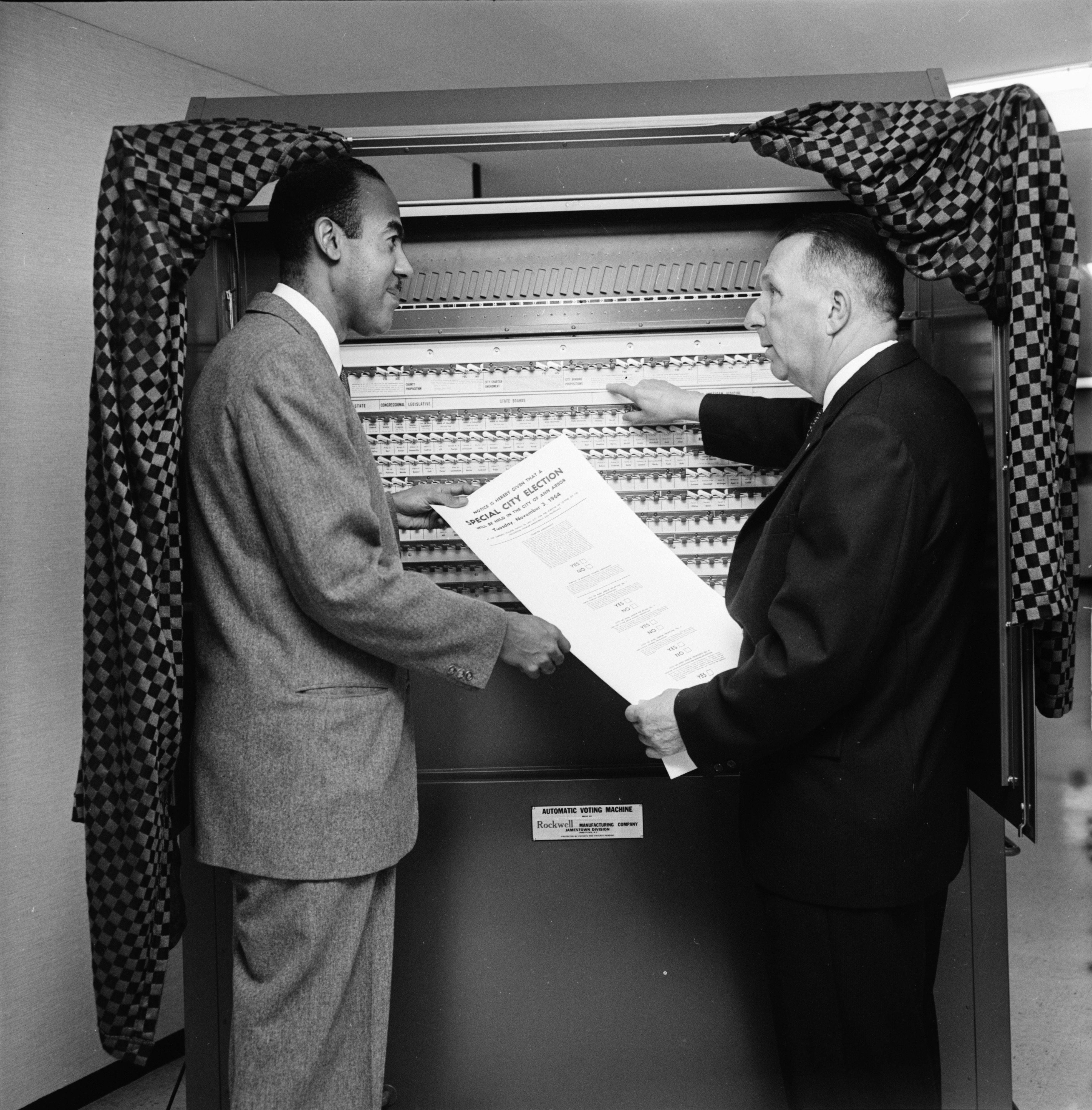 City Clerk Fred J. Looker and Walter Hill, director of the Ann Arbor Community Center, discuss public voter education program, October 1964 image
