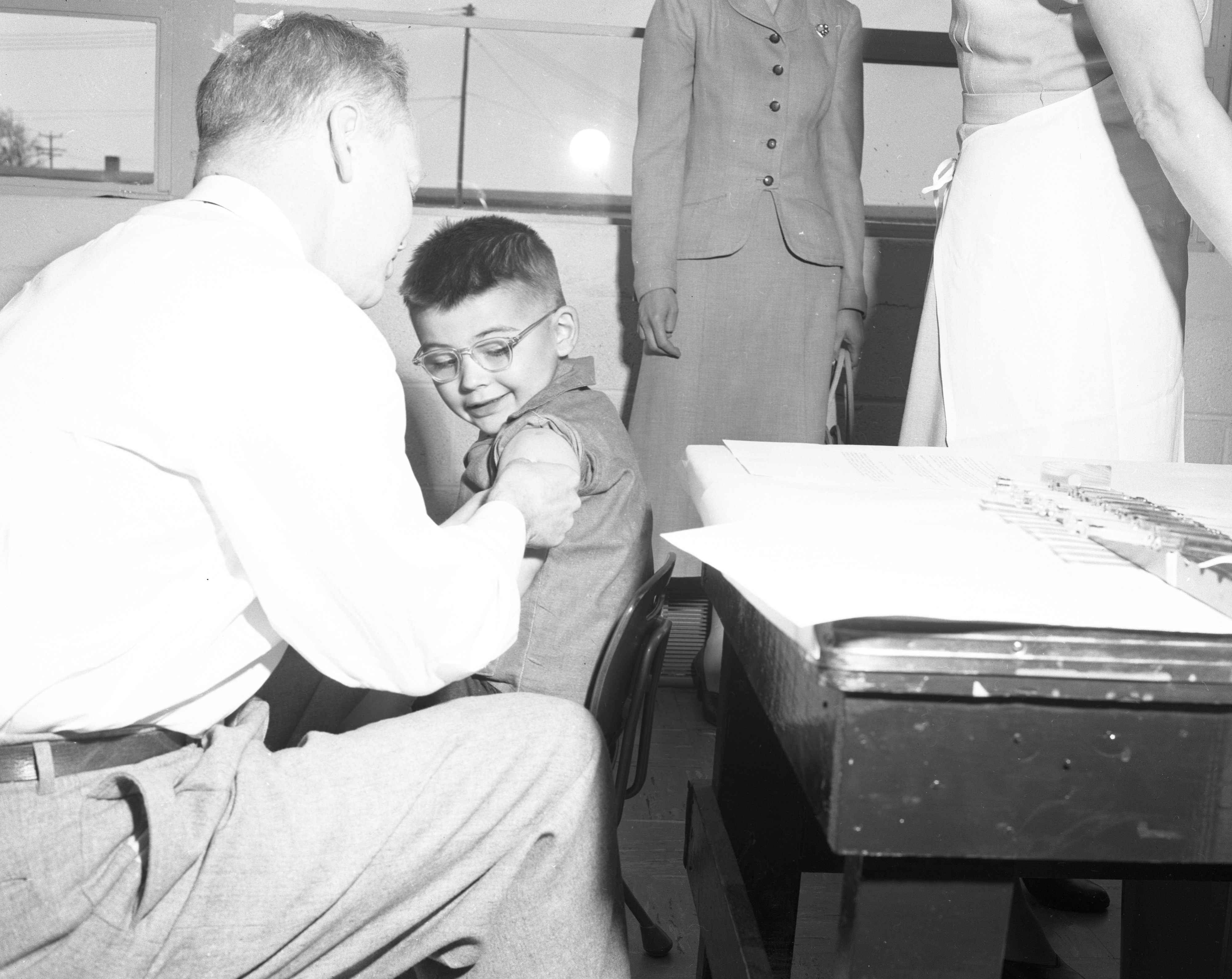 Doctor prepares young boy for polio vaccine, April 1955 image