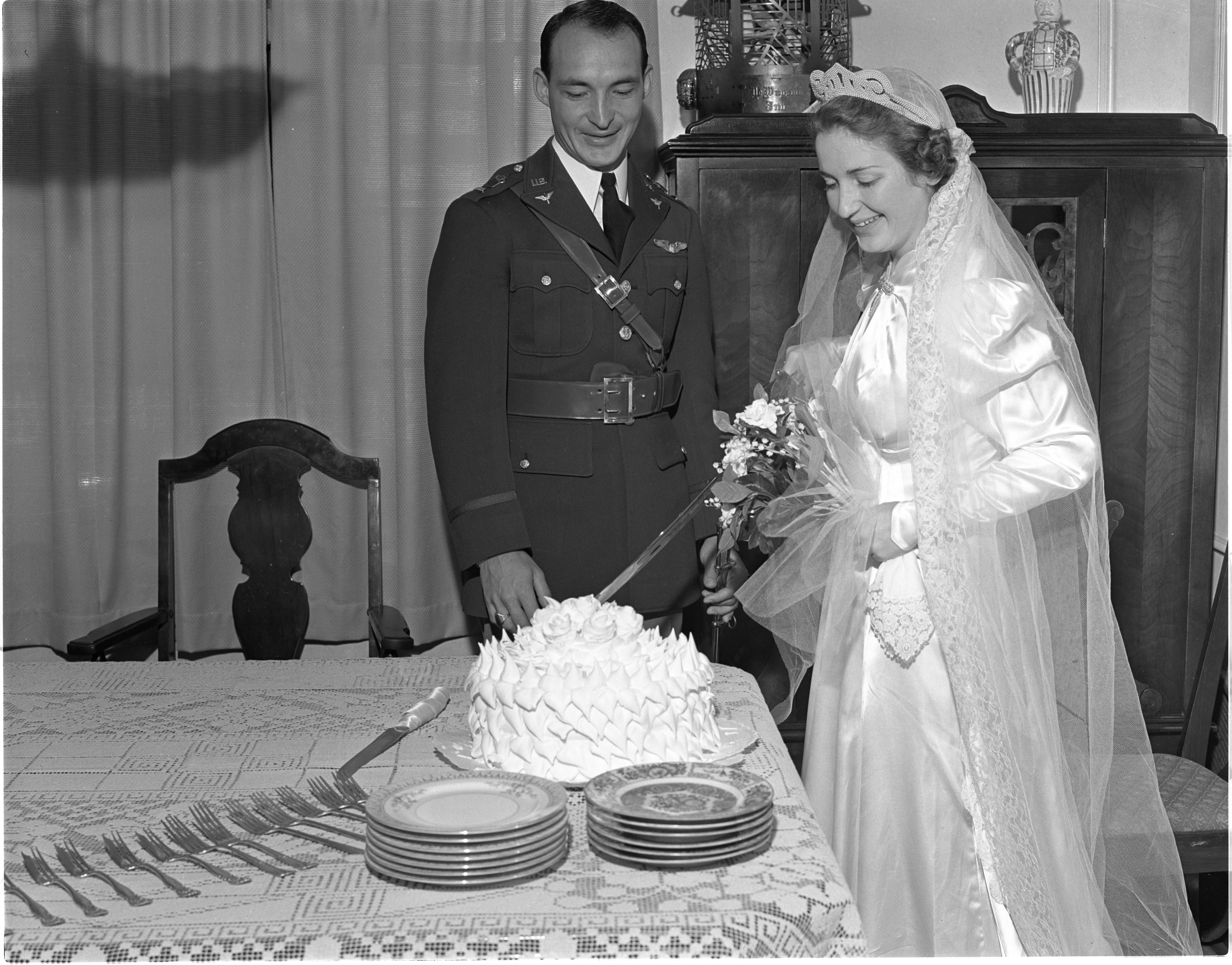 Lt. Harrie D. Riley Jr. Watches His New Wife, Felice, Cut Their Wedding Cake With A Saber - September 22, 1939 image