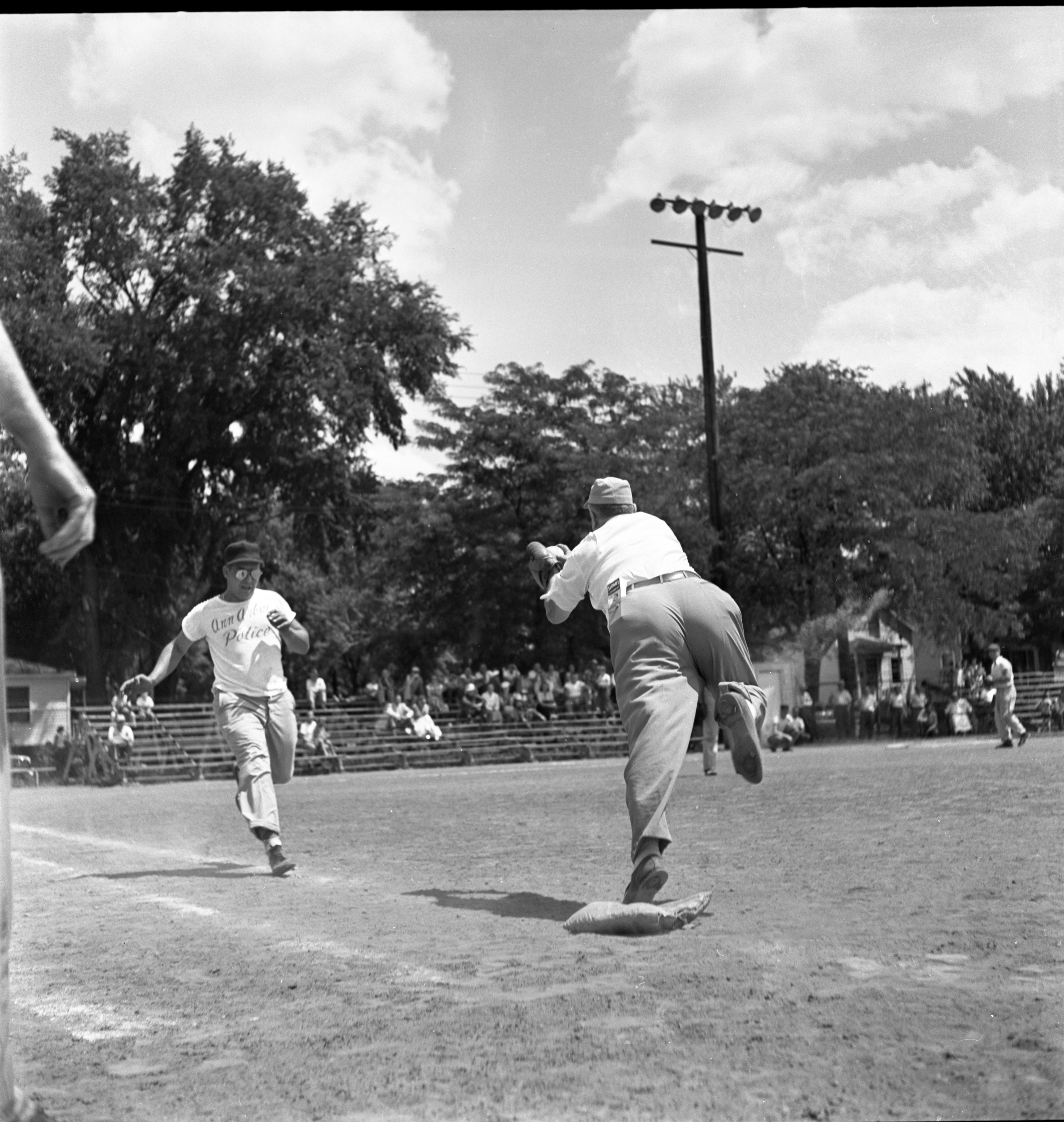 H. H. Caswell & John Spalding Meet On First Base At The City Council Vs. Police Softball Game, July 1953 image