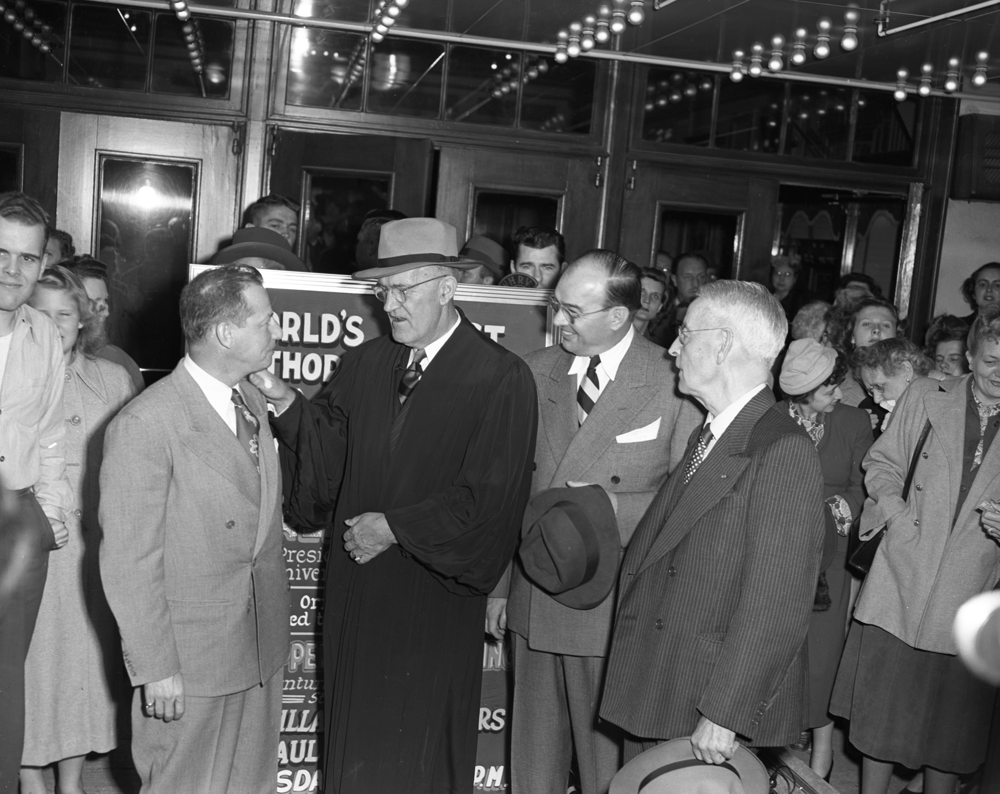 "Hollywood scriptwriter George J. Burke, Ann Arbor Mayor William E. Brown, Jr., and retired University vice-president Shirley W. Smith, at the world's first ""author's premiere"" outside the Michigan Theater, May 1949 image"