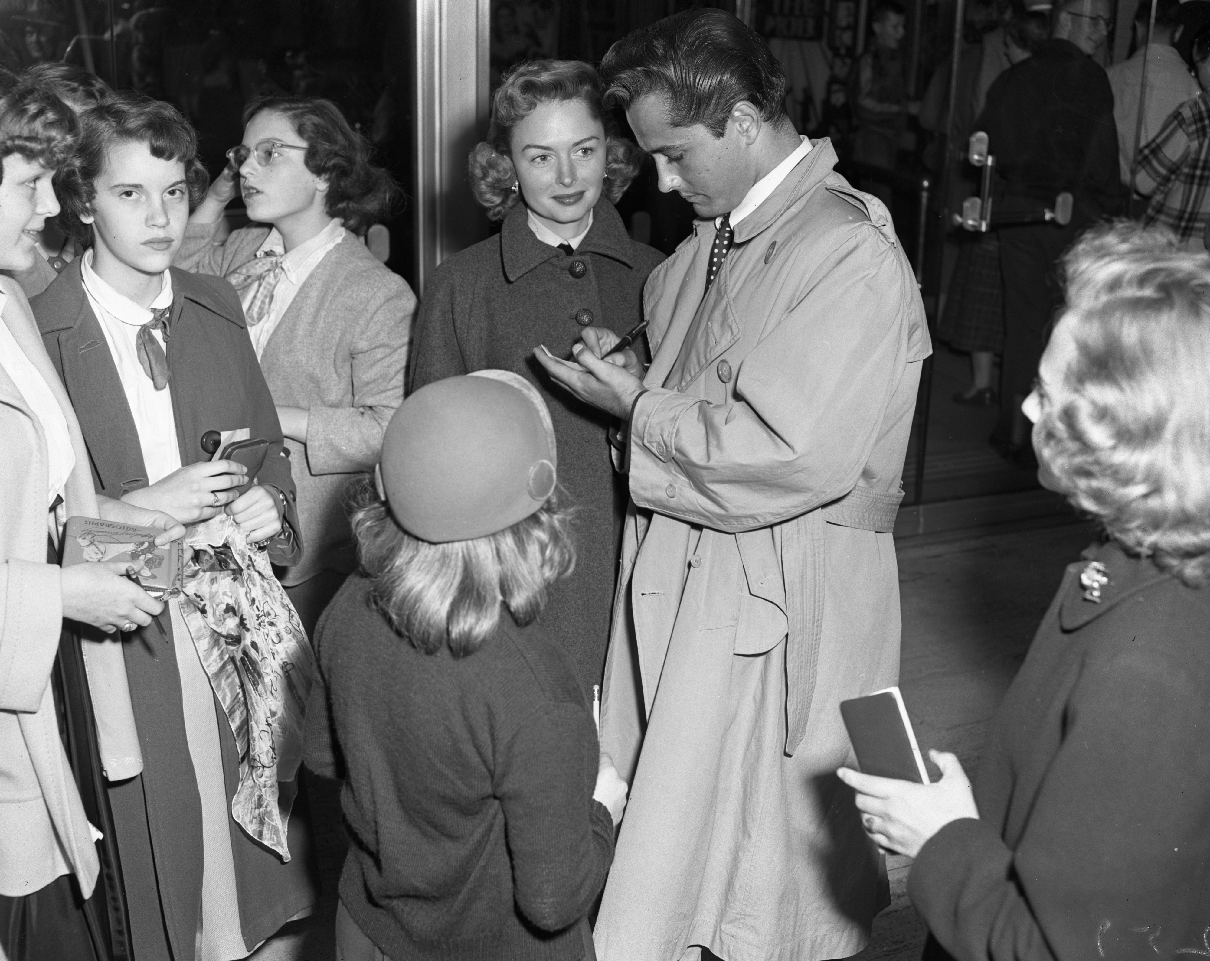 "Actors Donna Reed and John Derek sign autographs for fans at the Michigan Theater screening of ""Saturday's Hero,"" September 29, 1951 image"