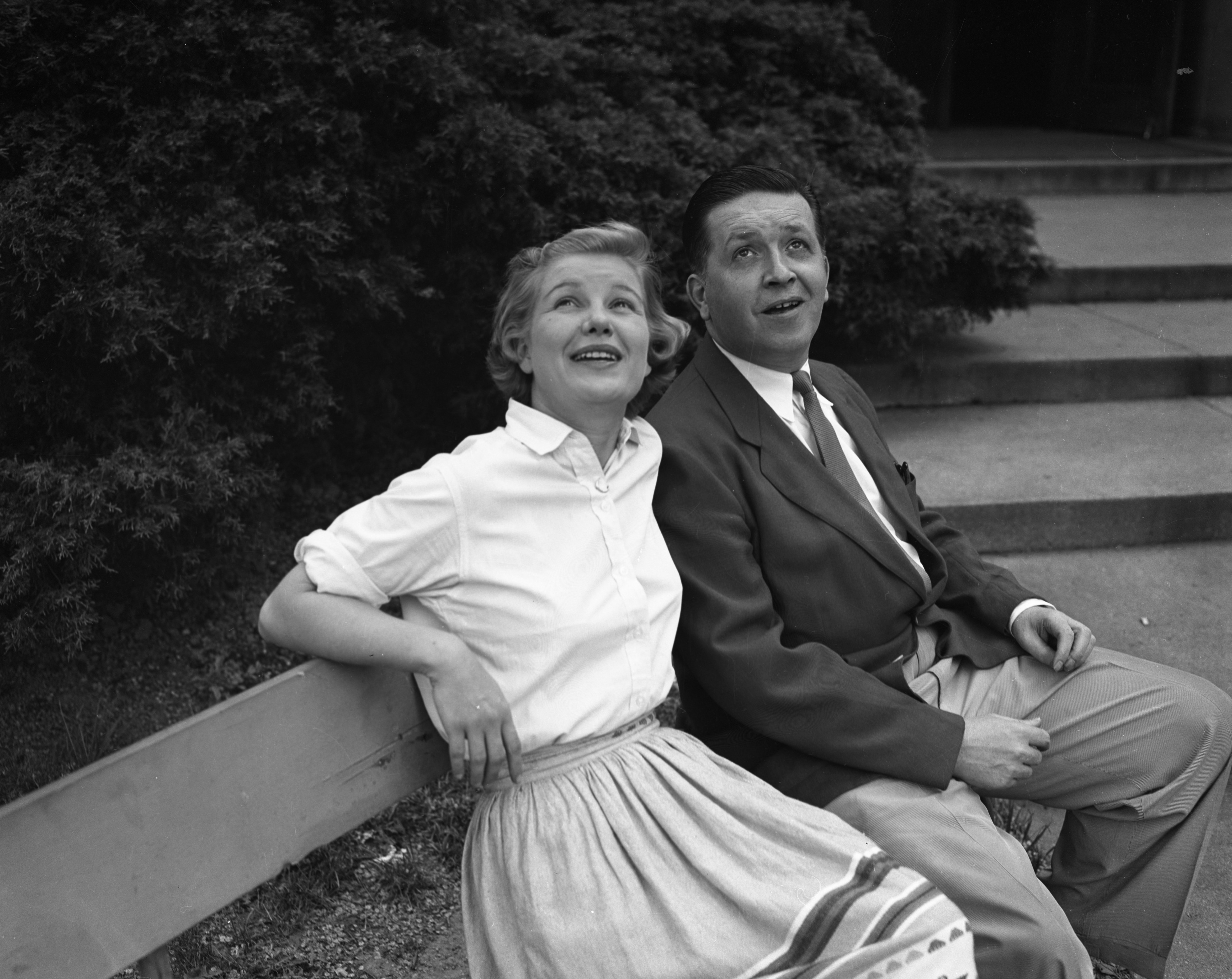 Actors Barbara Bel Geddes and Hiram Sherman on a bench outside the Michigan League, May 1954 image