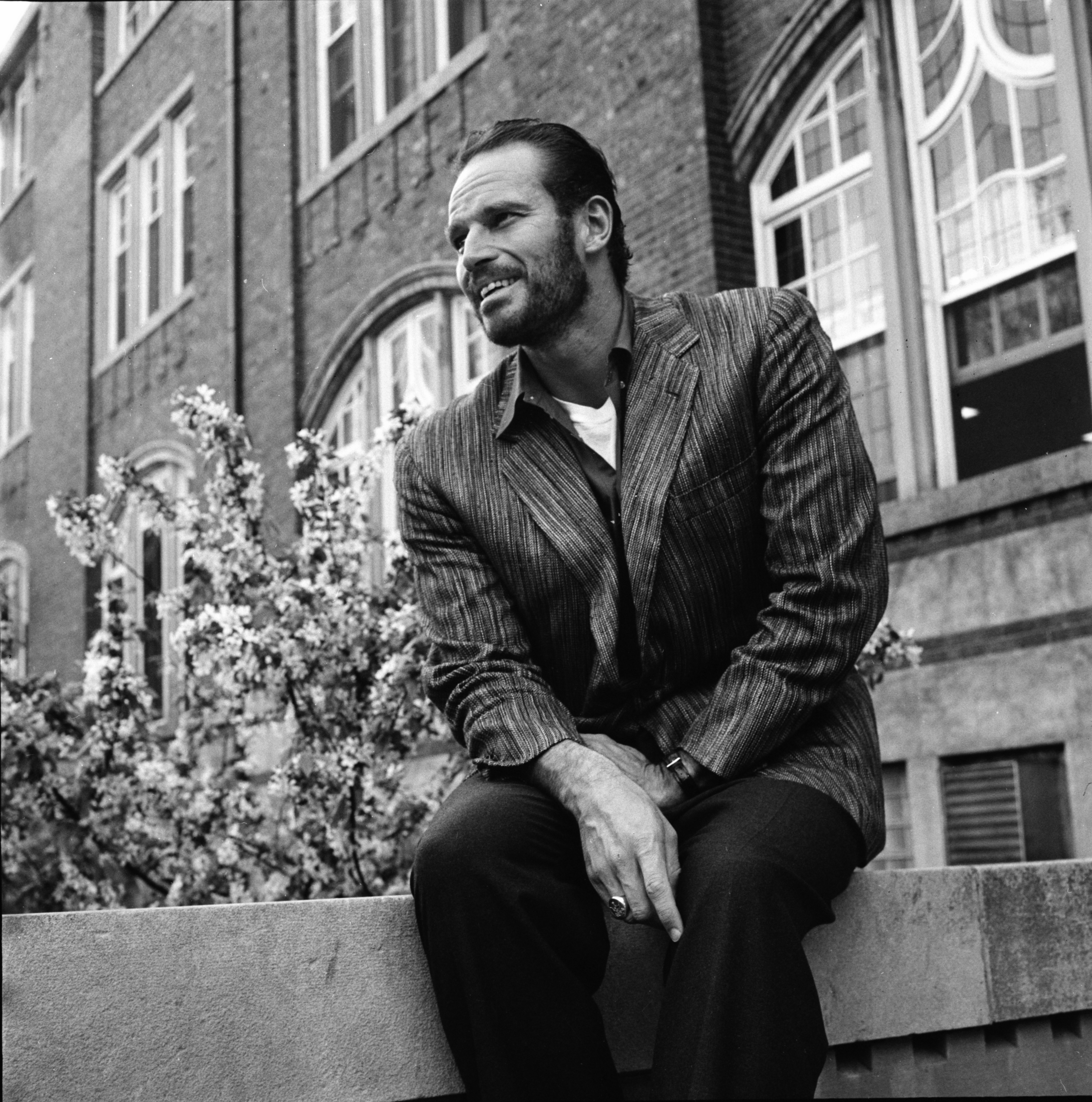 "Charlton Heston, starring in Ann Arbor Drama Season's ""Macbeth,"" sits outside the Michigan Union, May 1959 image"