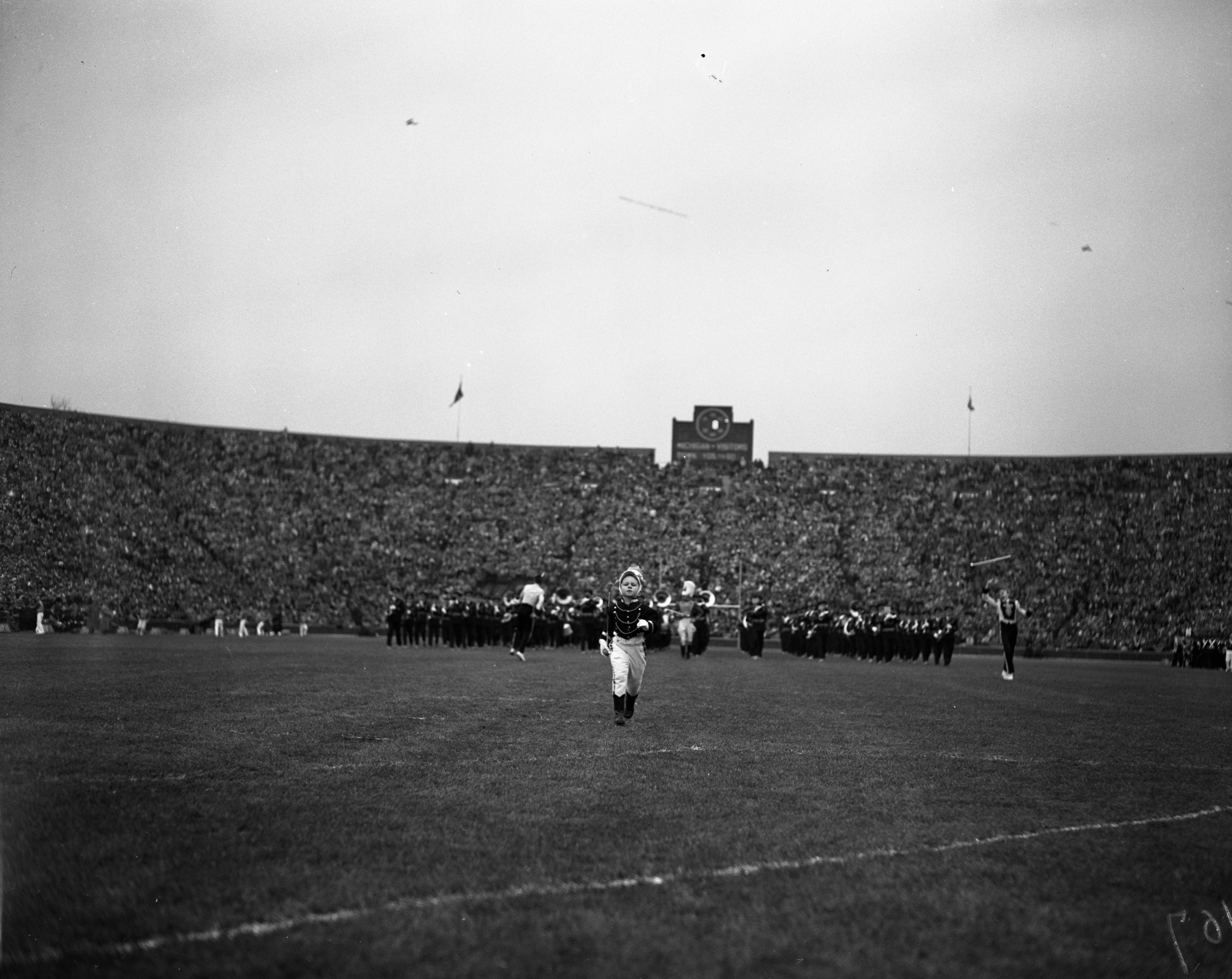 4-year-old Eugene Waxman leads the University of Michigan Marching Band down the field, November 1949 image