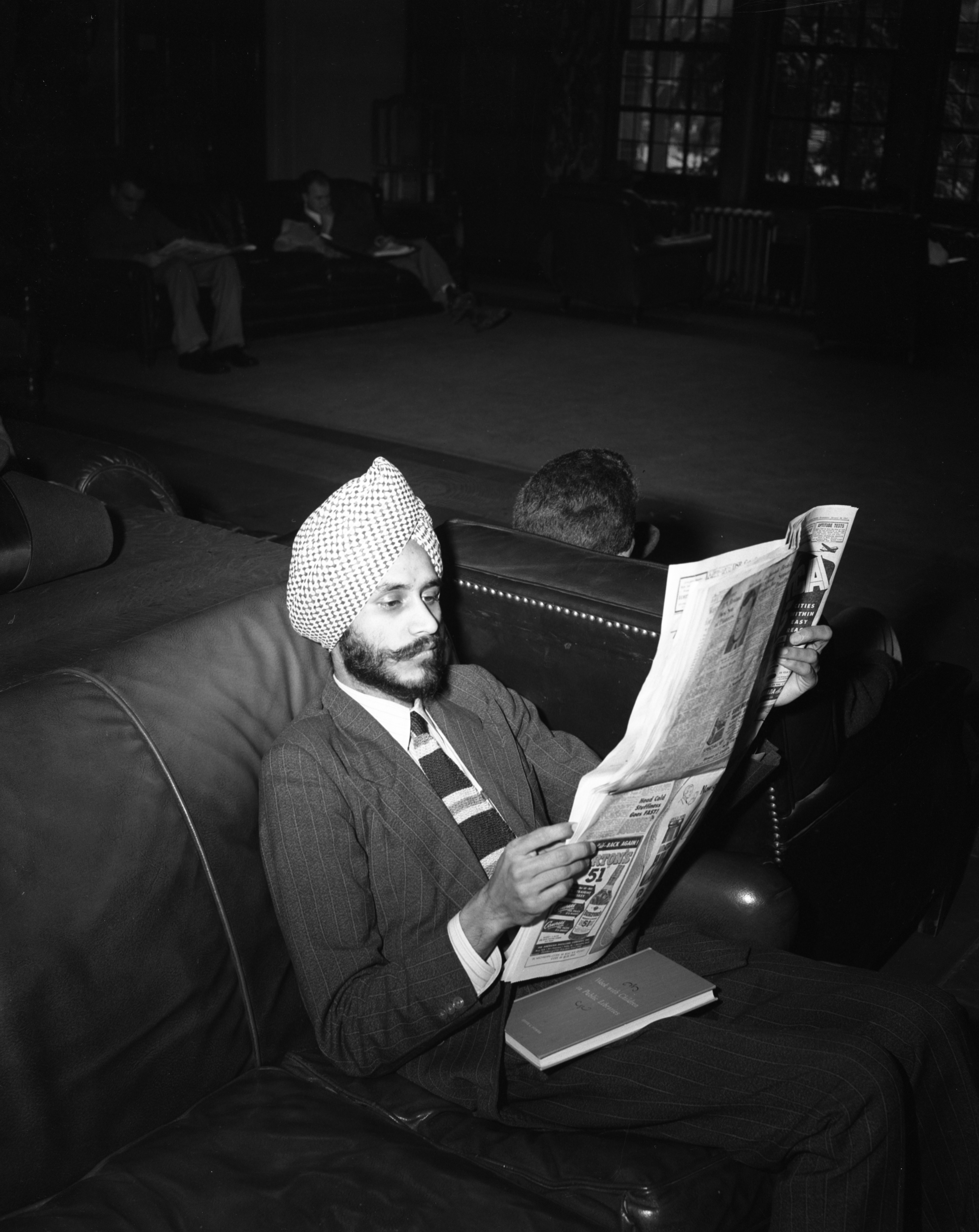 Student From India Reading Newspaper In Michigan Union, February 1949 image
