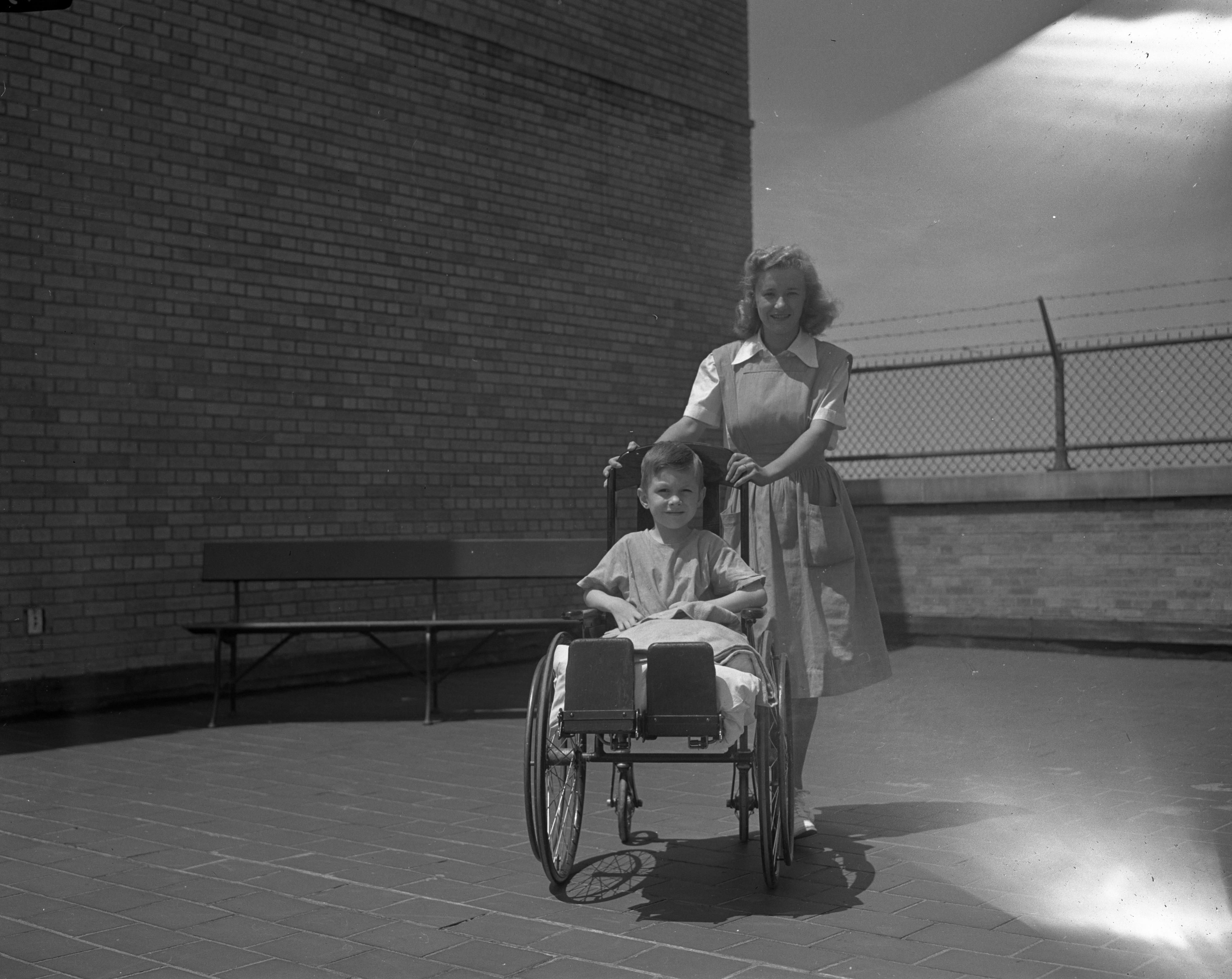 Red Cross Nurse's Aide Elizabeth Langford with young patient, May 1942 image