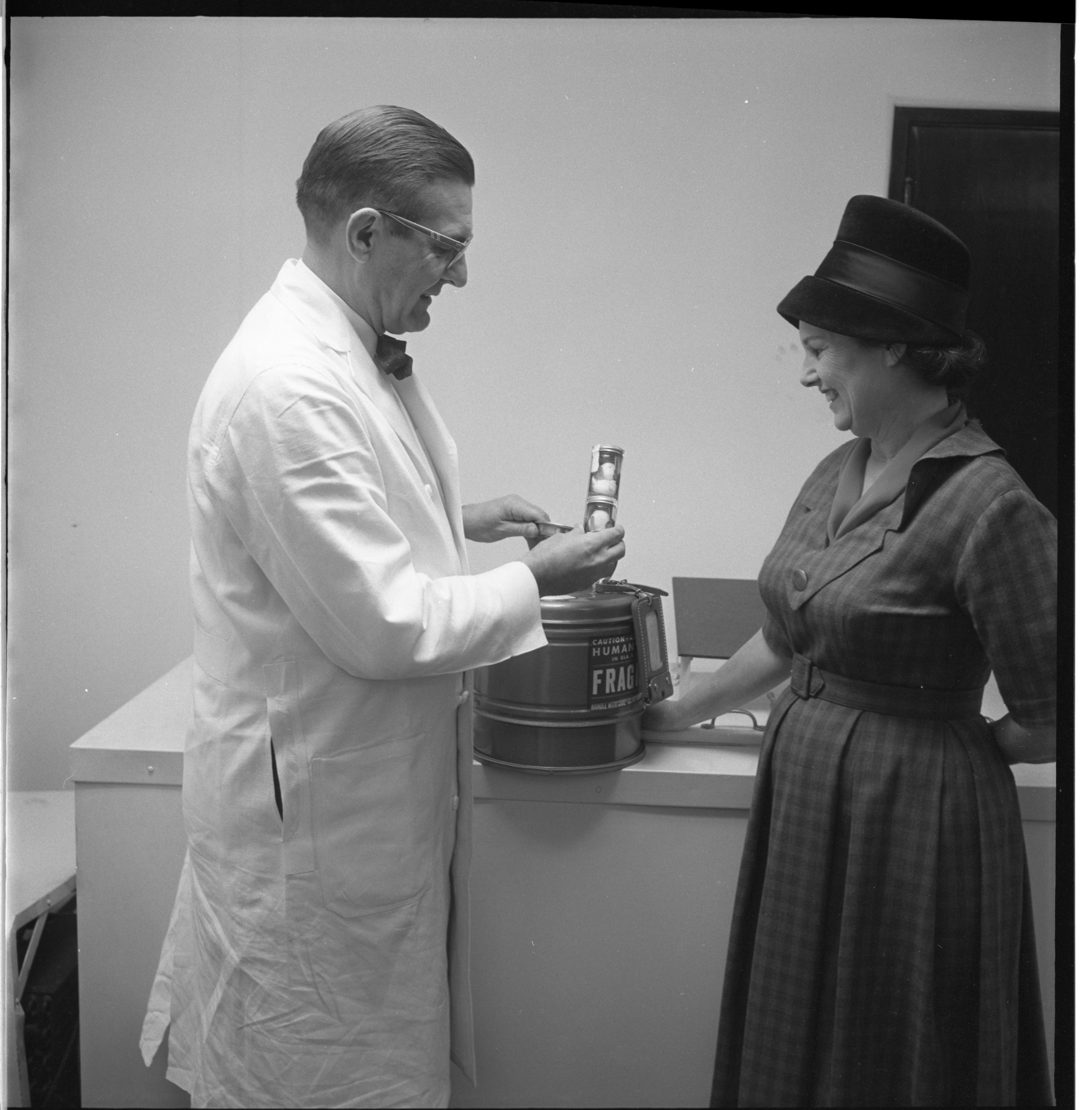 Mrs. Wilfred Graf, Of The Numa Club, Donates A Container Used For Transporting Donor Eyes To Dr. John Henderson At The Michigan Eye Collection Center, January 1962 image