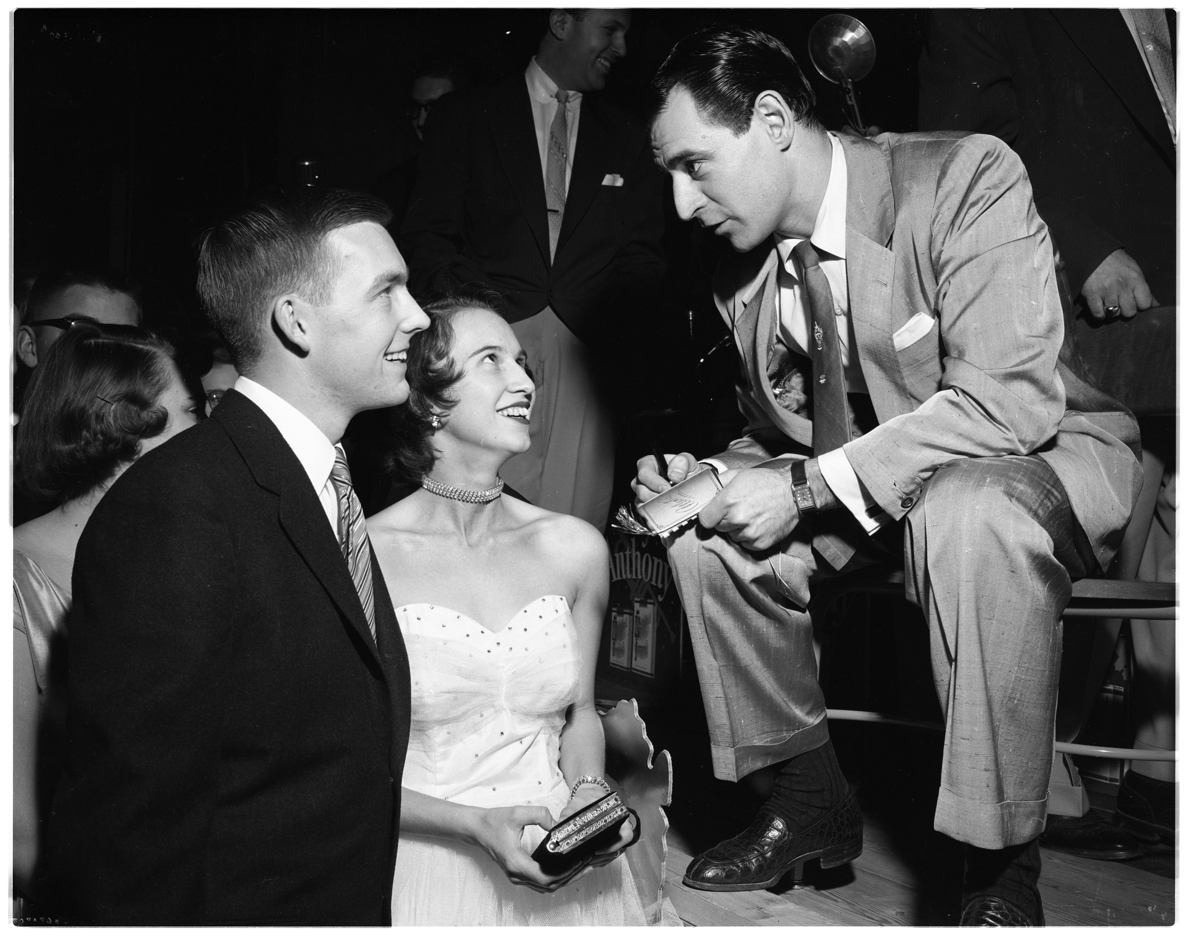Ray Anthony, bandleader, talks to talks to Mr. and Mrs. Russell AuWerter II at the J-Hop, February 5, 1954 image