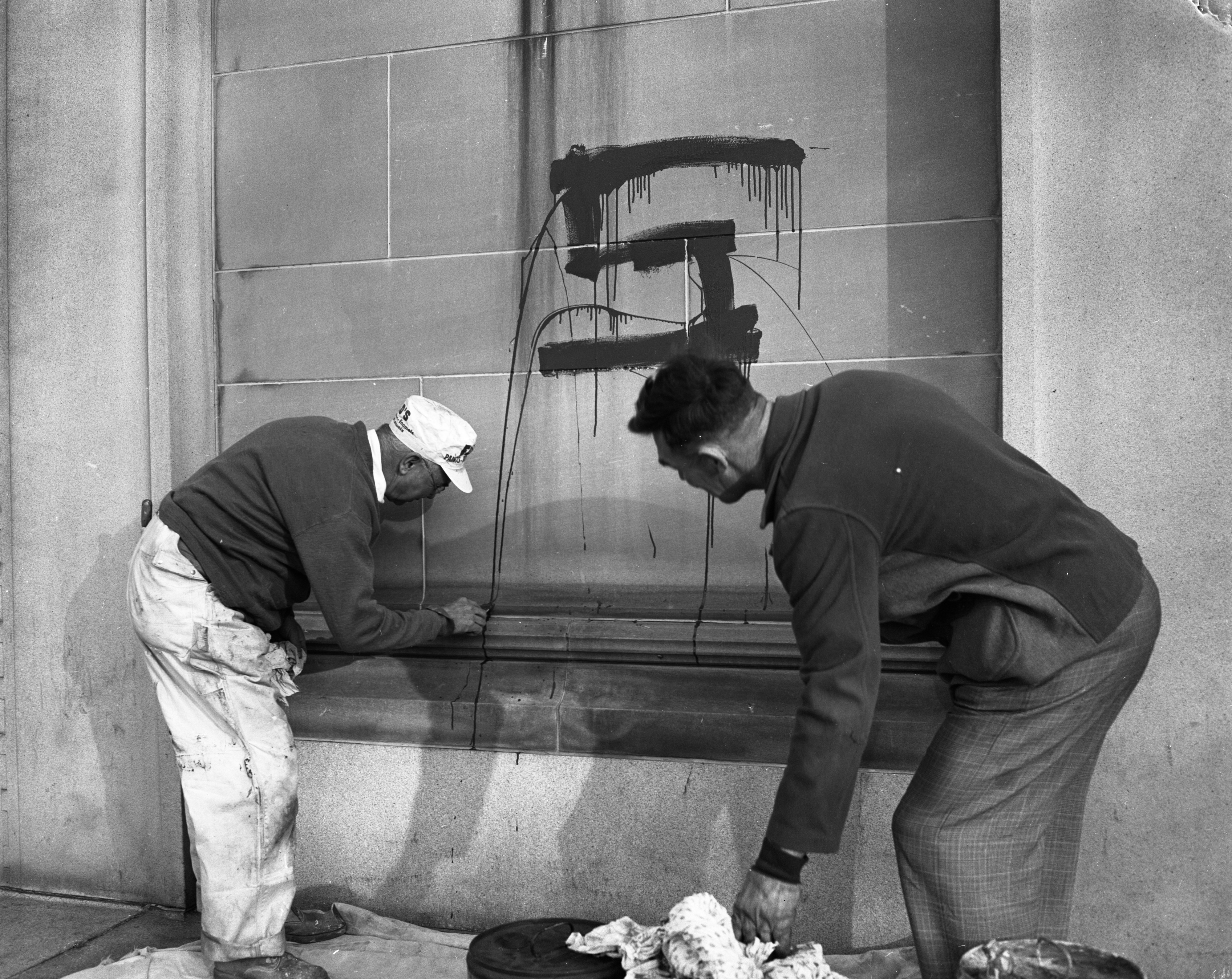 Michigan State College students paint the U-M campus green and white prior to the big game, November 1954 image