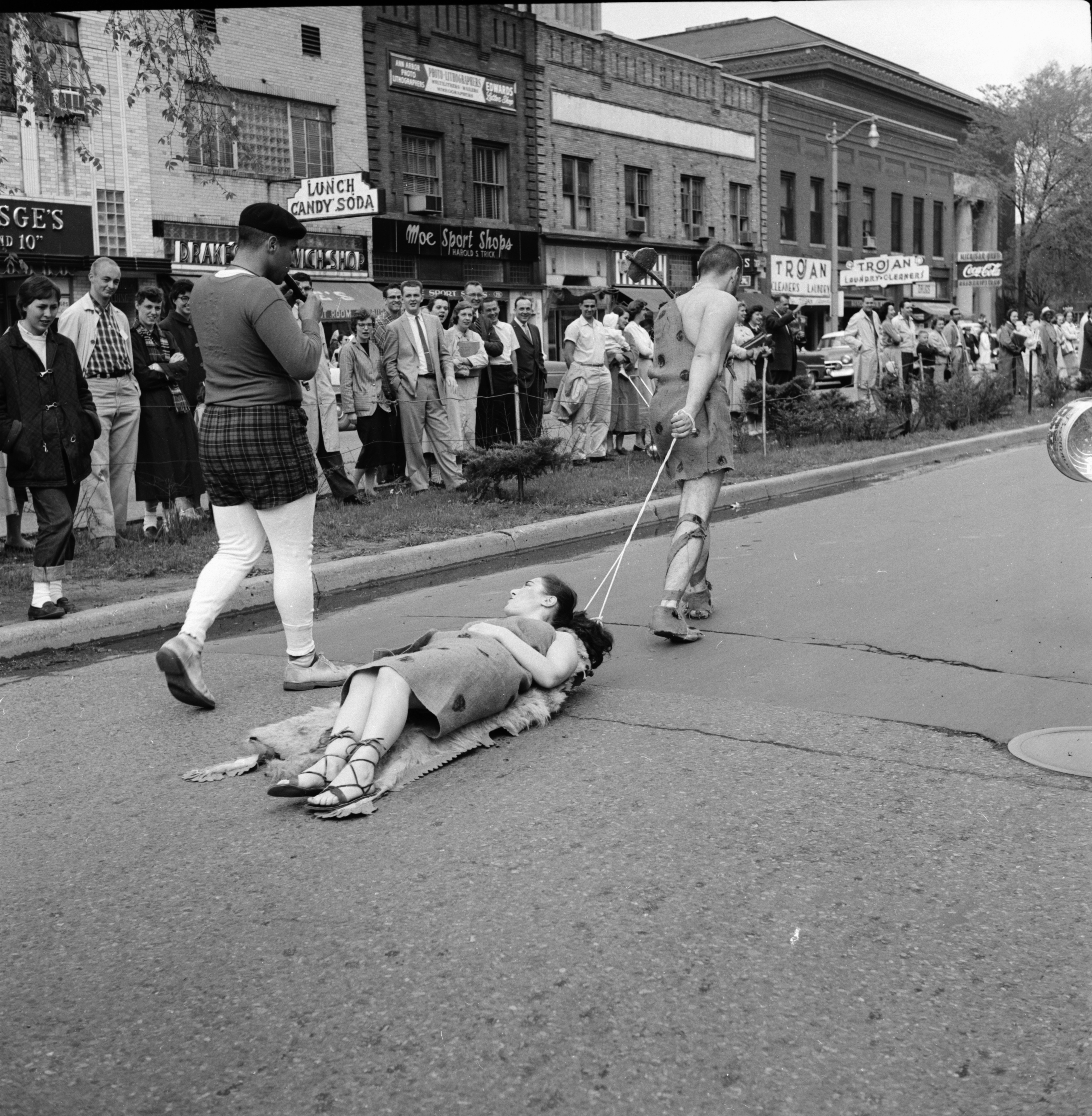 "A cave man drags his woman along North University during UM's ""Spring Weekend"" parade, May 1957 image"