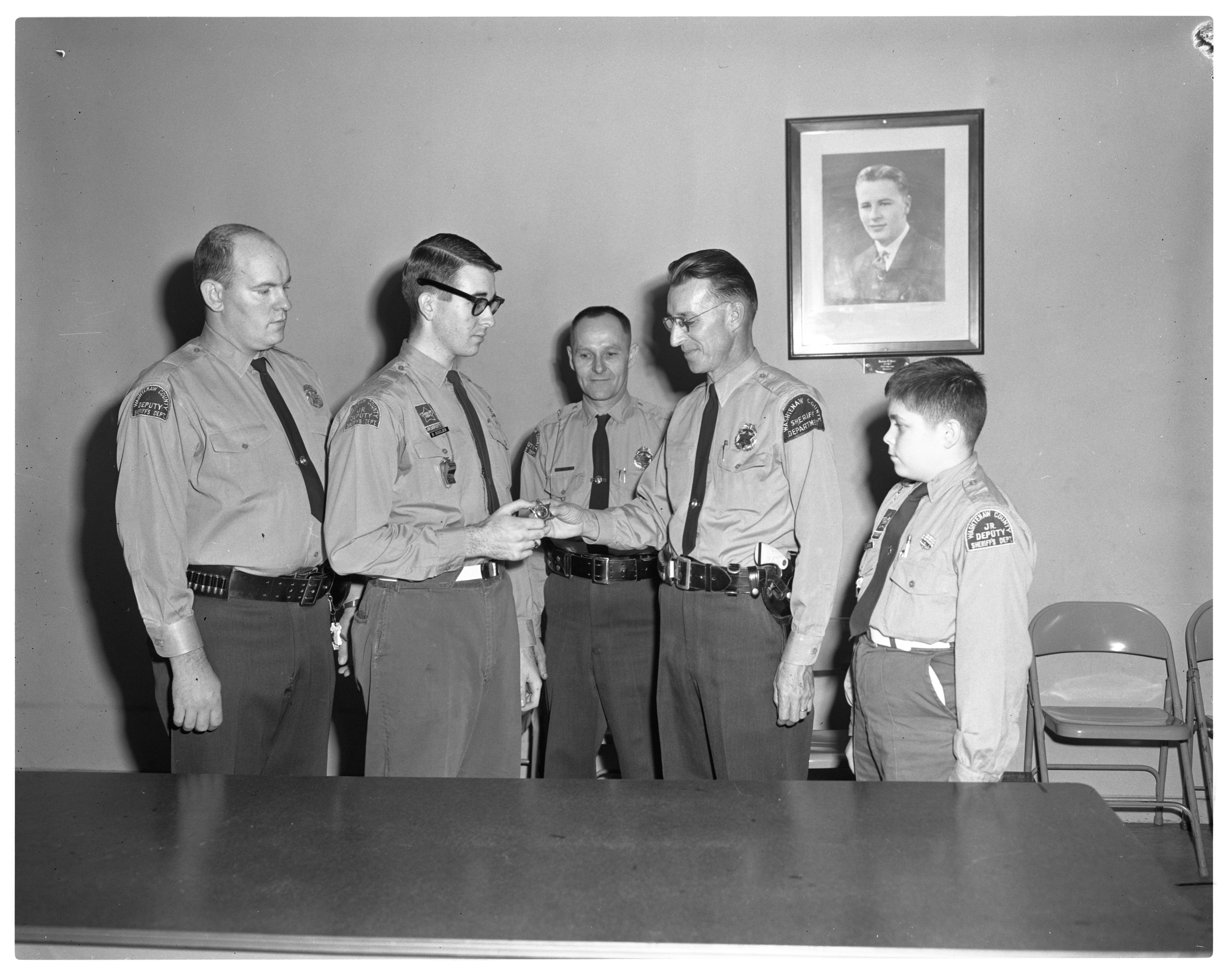 Robert C. Britton Awards Badge to Junior Deputy Inspector Captain Bud Sigler, December 1963 image