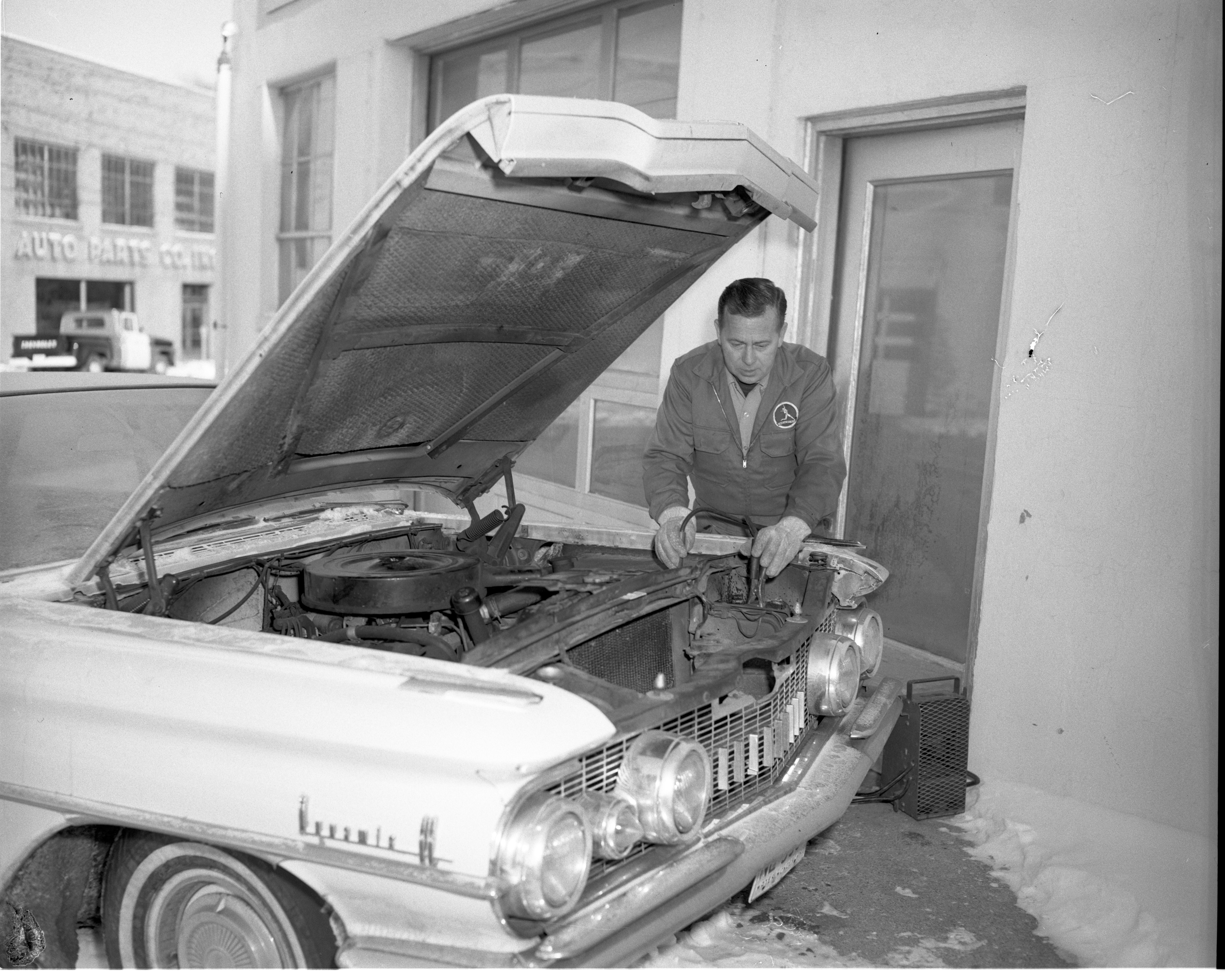 Bill Sprentall Charges A Battery At Sprentall's Service, January 1963 image