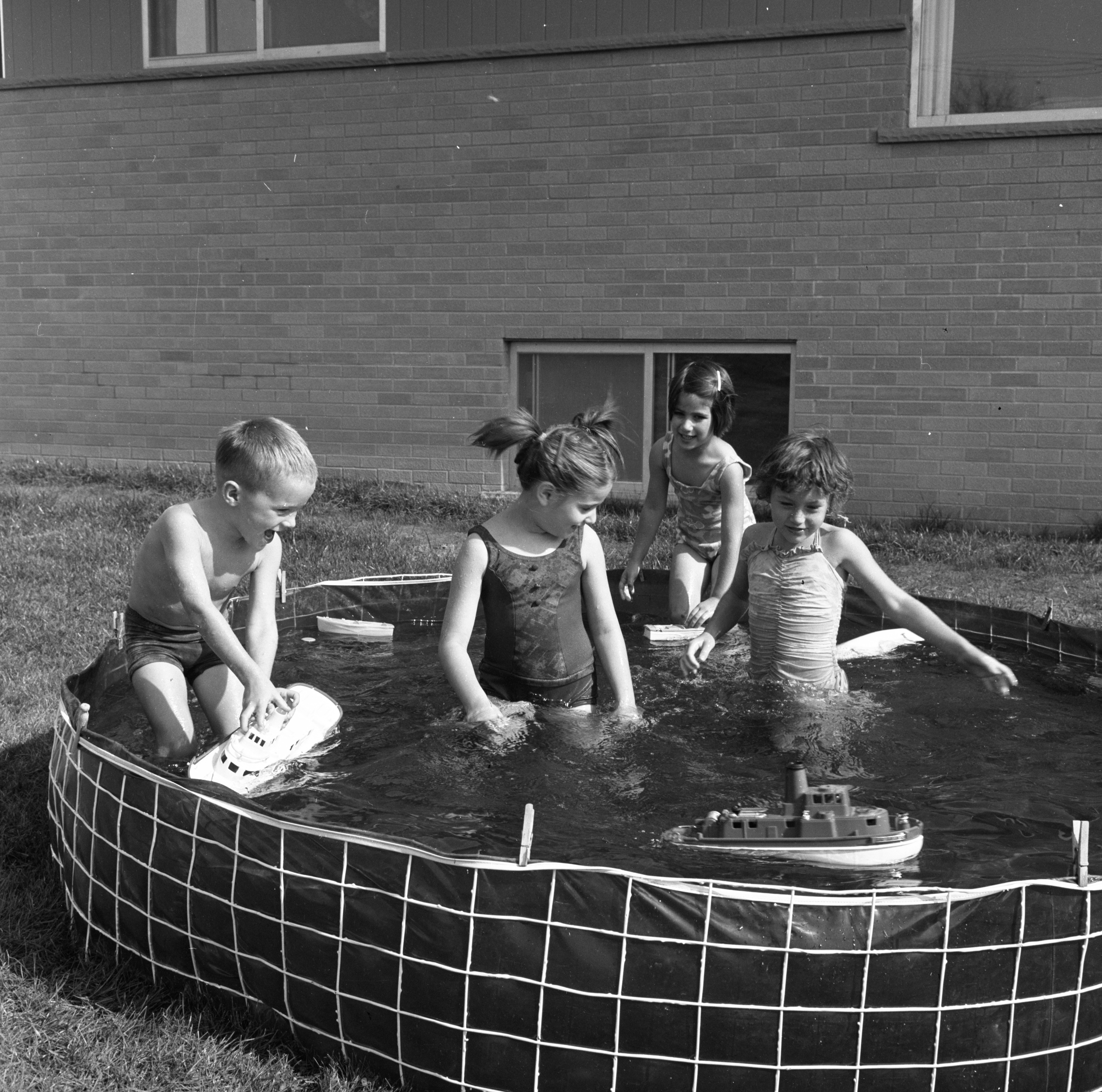 Children Enjoy A Wading Pool In Warm October Weather, October 1963 image