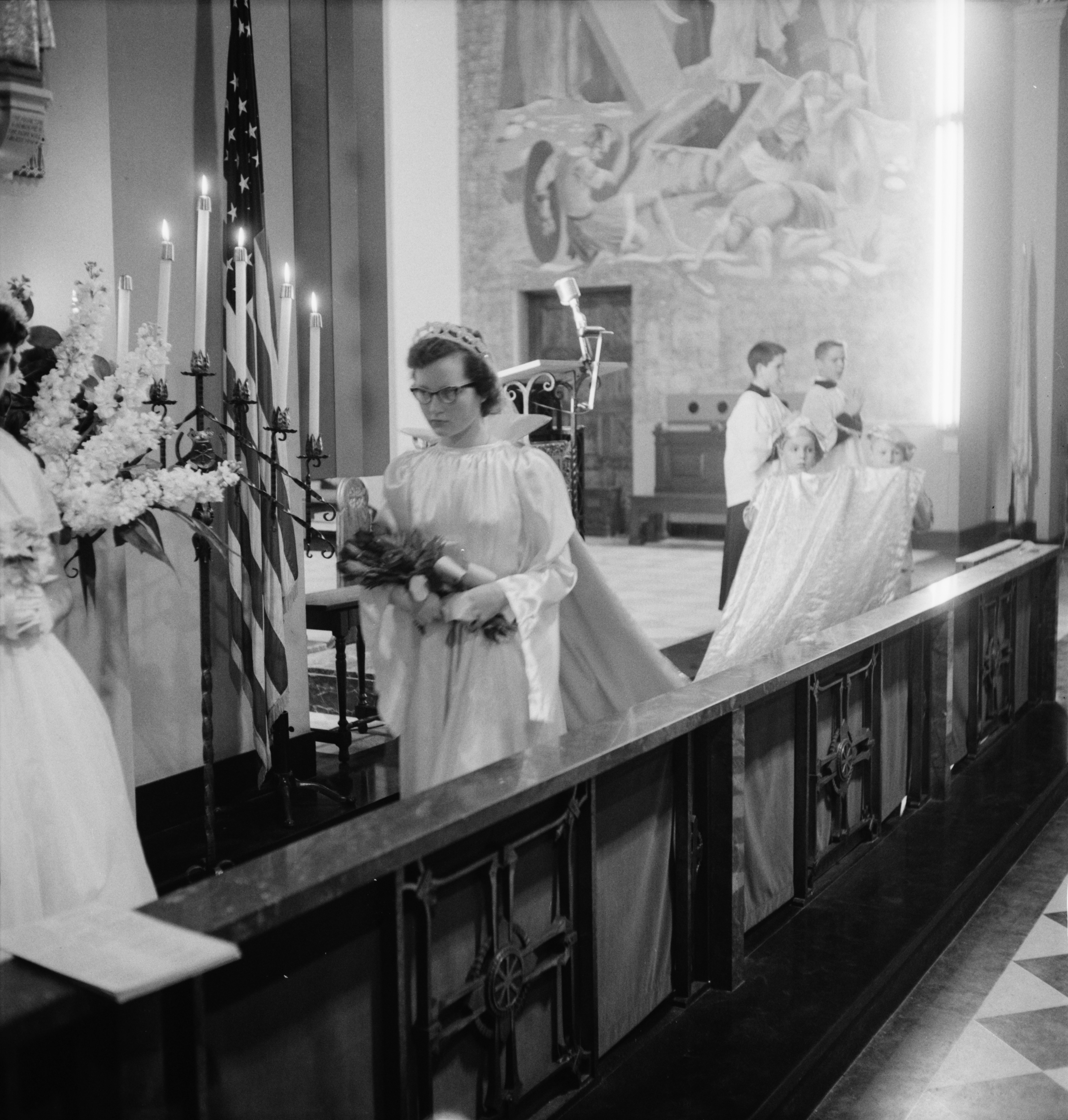 May Queen Bonnie Samar Carries Flowers For Mary During The May Crowning Ceremony At St. John's Catholic Church In Ypsilanti, May 1957 image