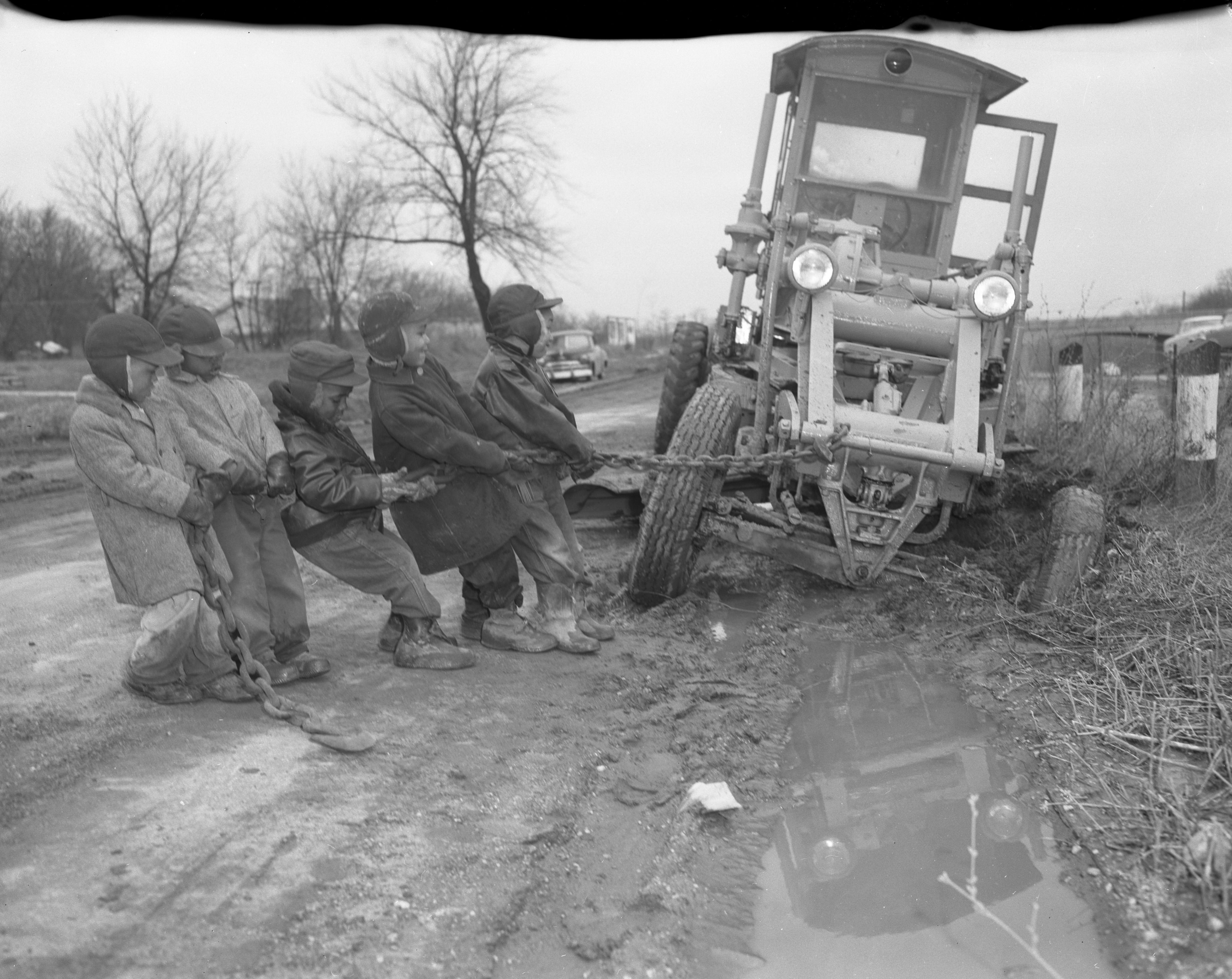Ypsilanti Boys Pull Hard On Stuck-In-The-Mud Road Grader, April 1957 image
