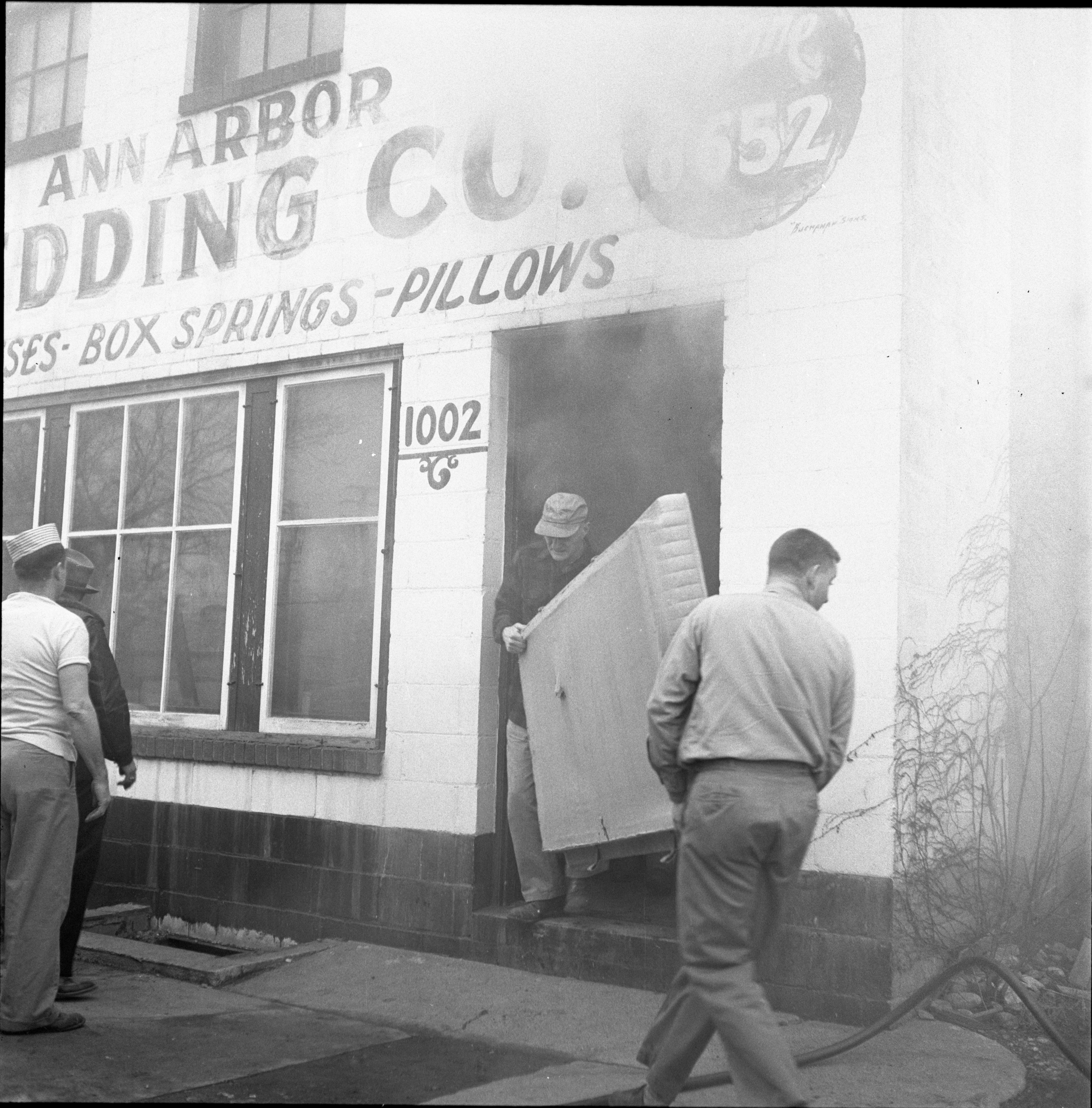 Mattresses Are Carried Out Of The Burning Ann Arbor Bedding Co. Building, February 1957 image