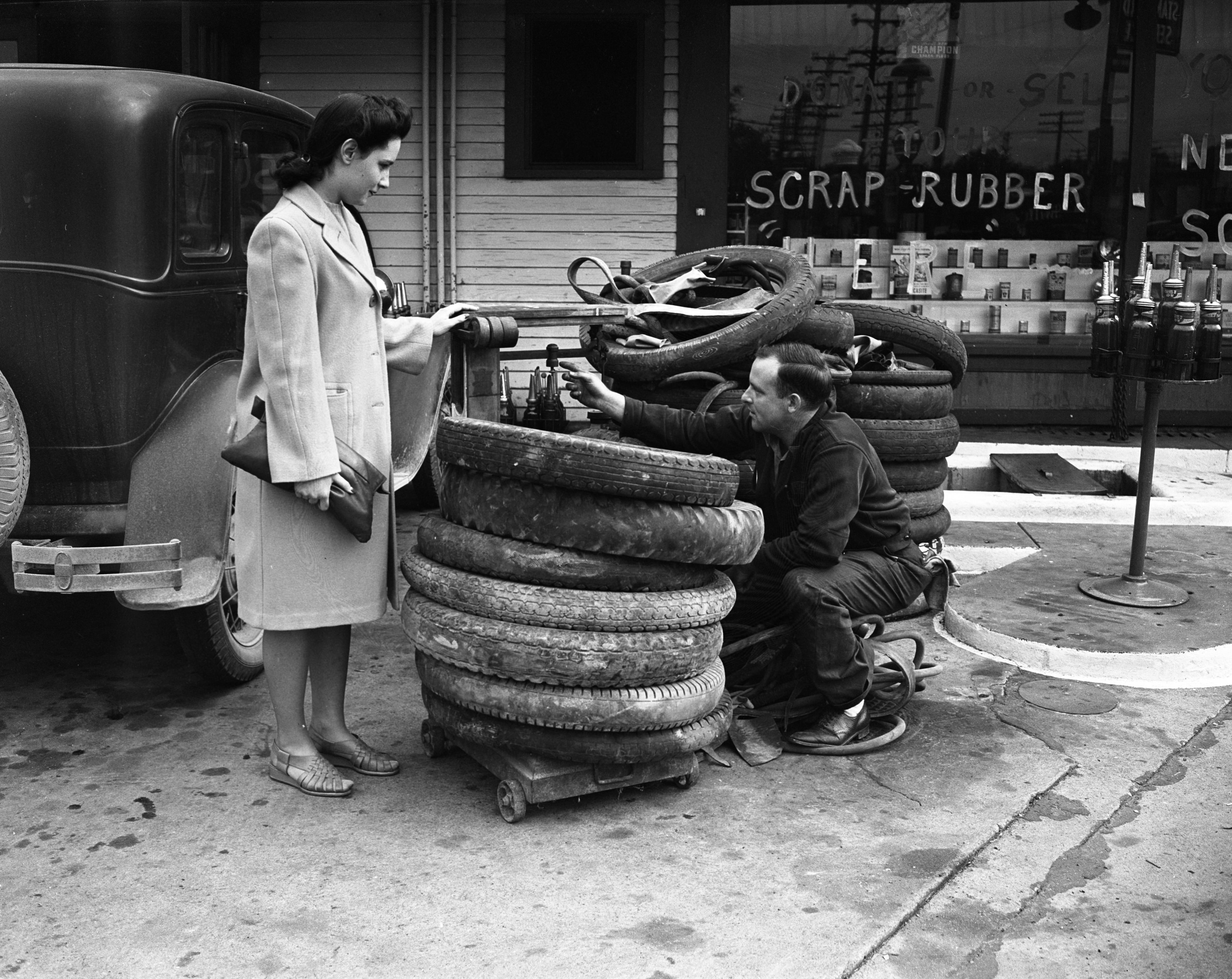 Mary Meyers and Harold Harris inspect a pile of scrap rubber for collection, June 1942 image