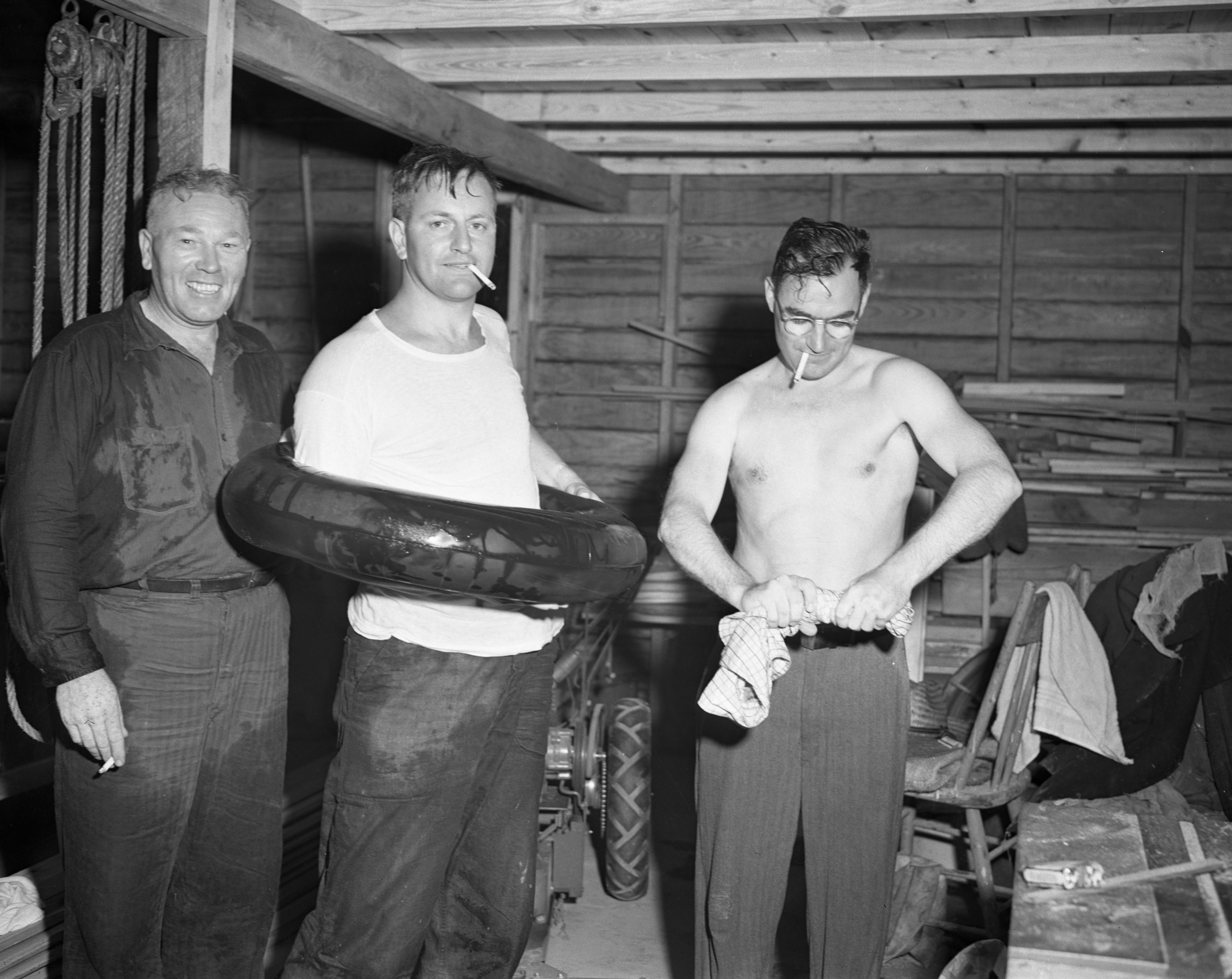 Ann Arbor News Employees Red Losey, Karl Horning, and Charlie Westenfeld, wring out clothing at Woodlawn Lake, April 1950 image