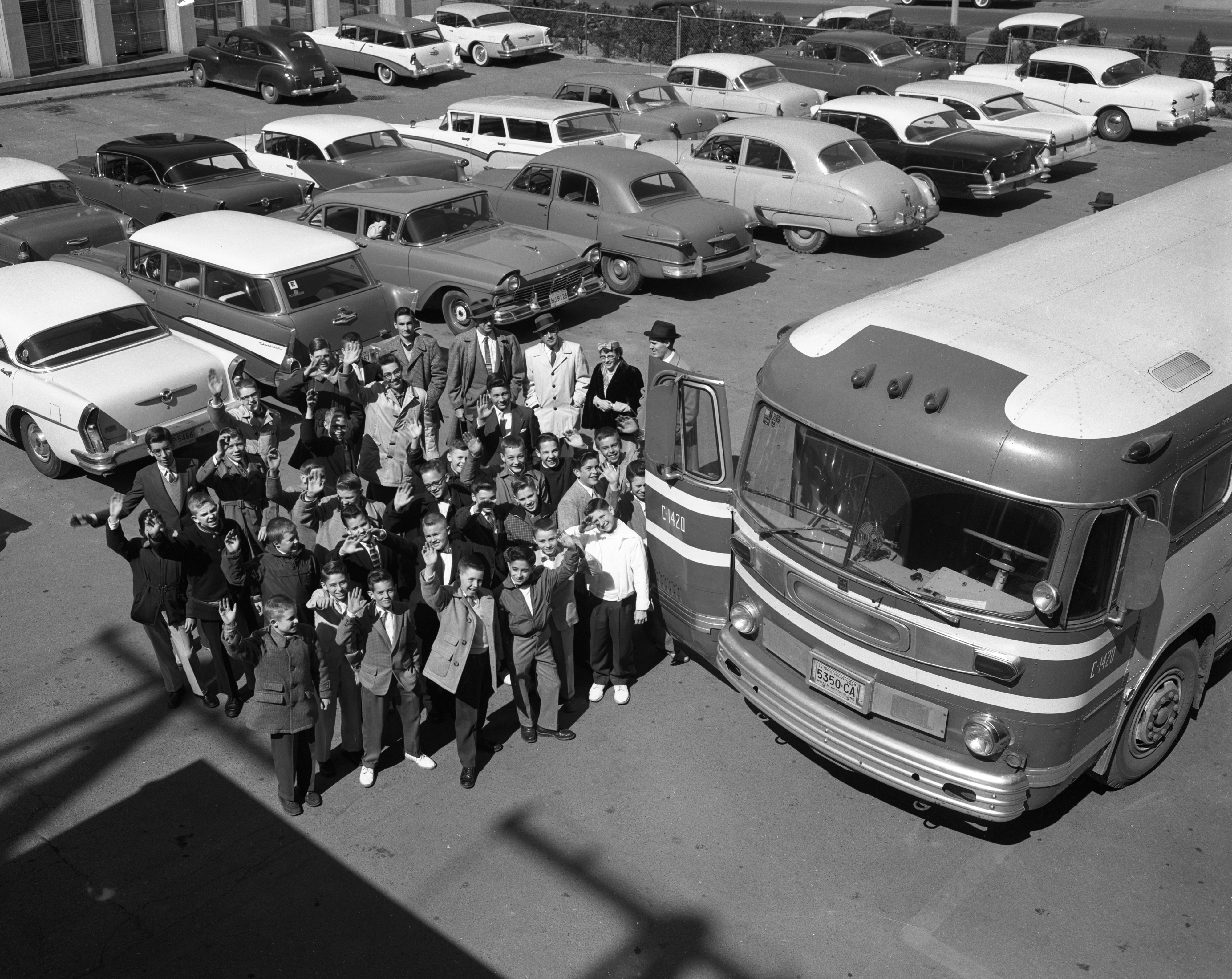 "Ann Arbor News carriers get ready to board a charter bus to Detroit to ""Cinerama,"" March 1958 image"