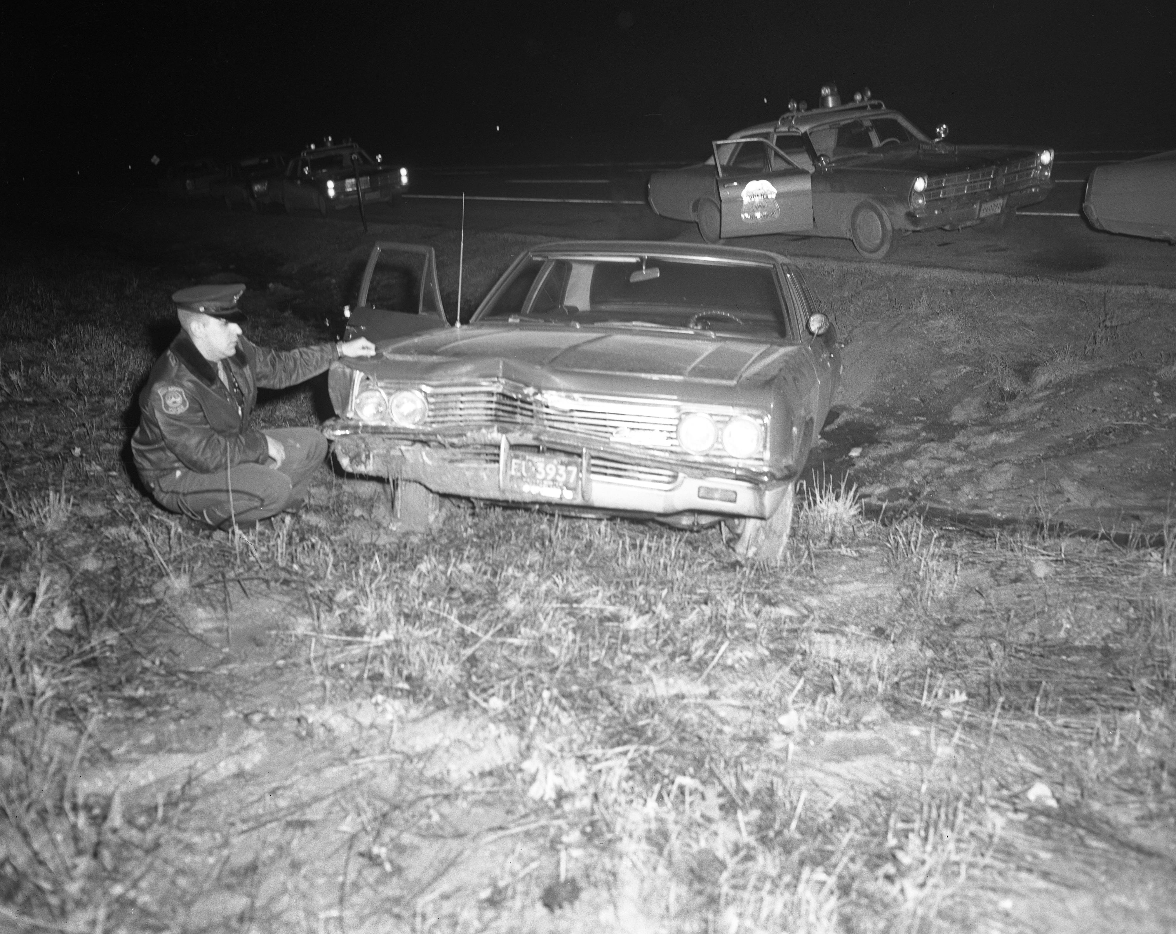 Ann Arbor Police Patrolman Richard Anderson Checks Robbery Getaway Car Following Chase, March 1967 image