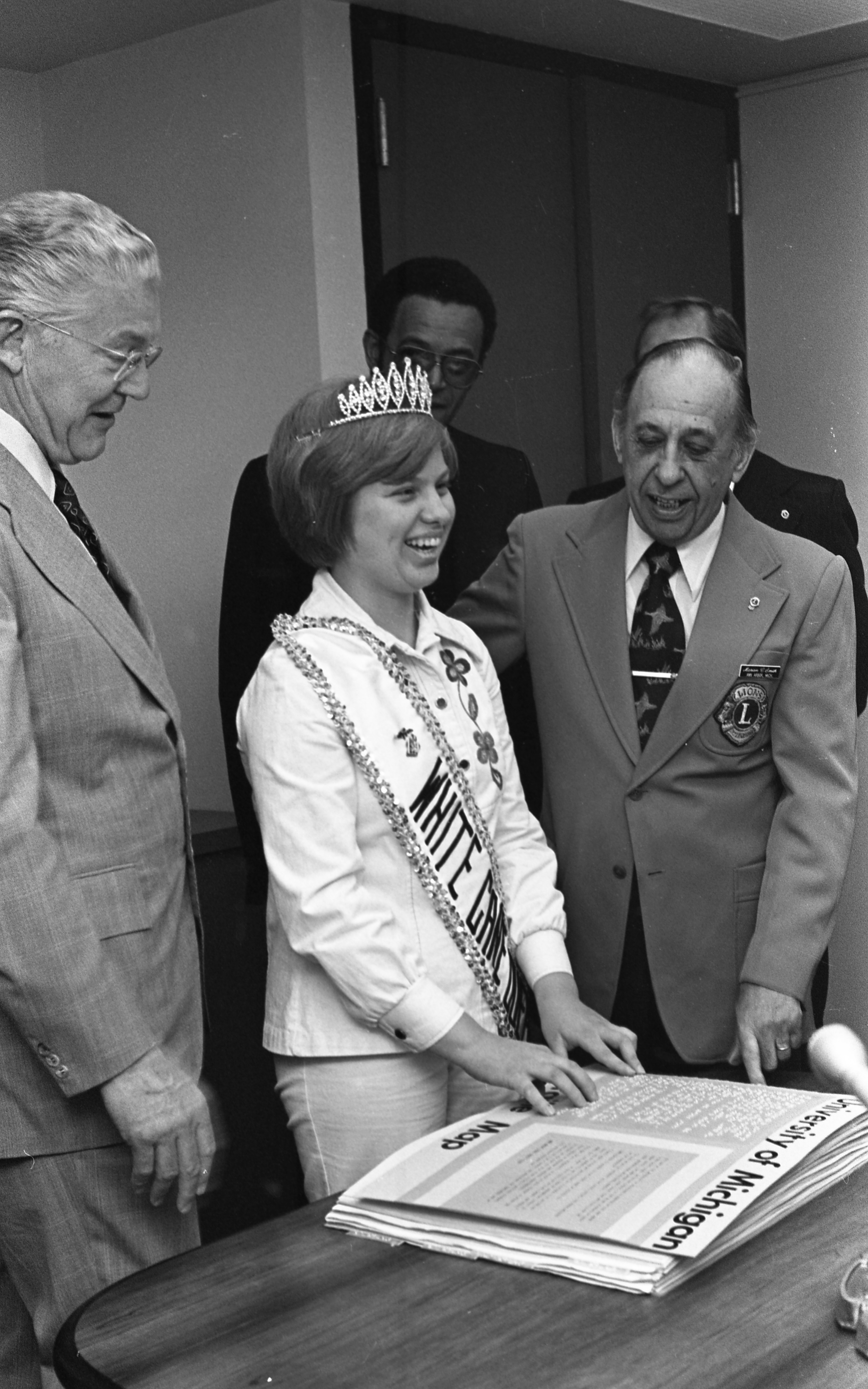 Braille Campus Maps Are Presented To University Of Michigan President Robben Fleming By Marion Smith, Ann Arbor Lions Club, & Christine Smith, Michigan Lions White Cane Queen, April 1977 image