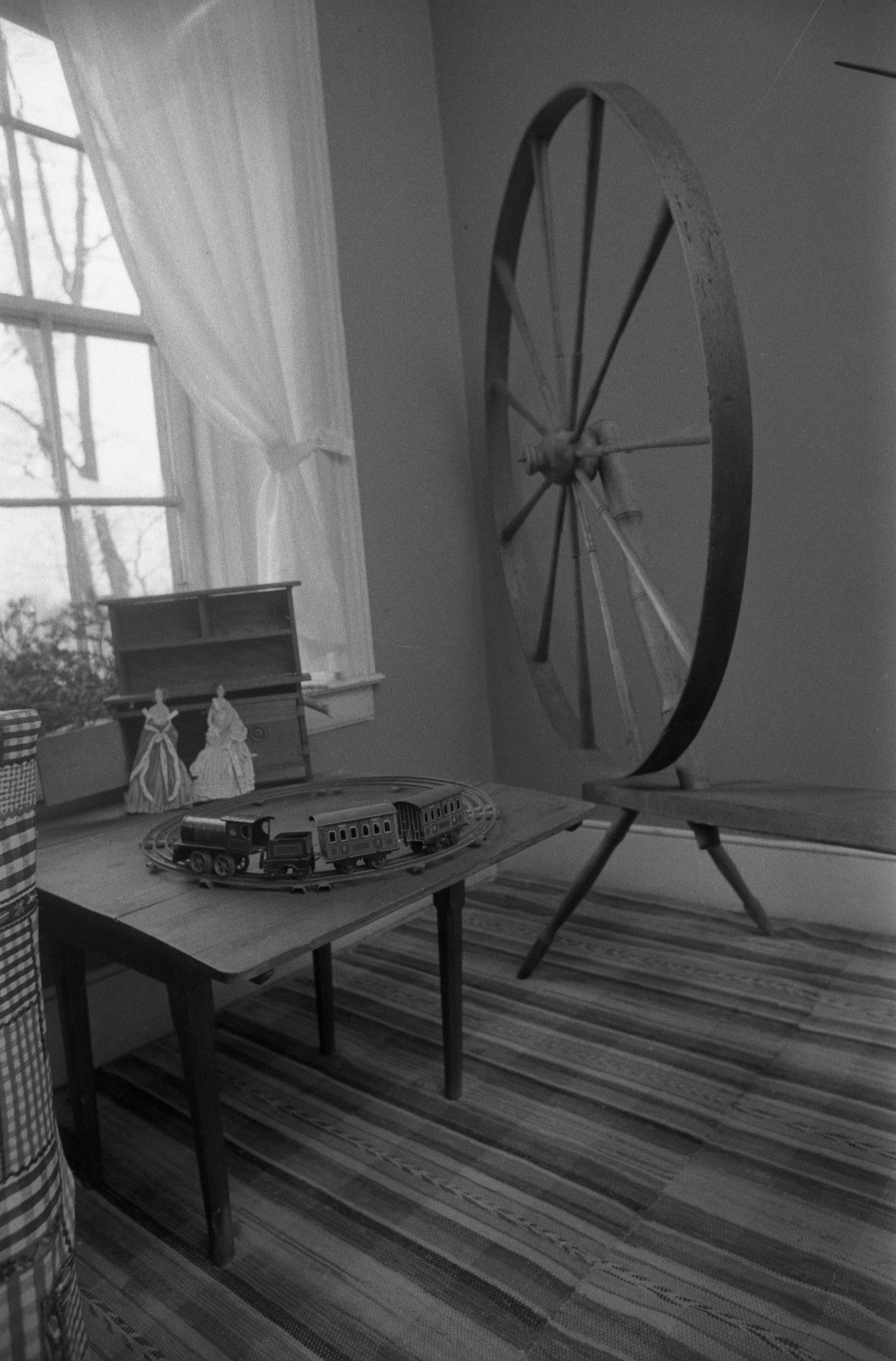 Spinning Wheel Next To Toy Train At Cobblestone Farmhouse, December 22, 1980 image
