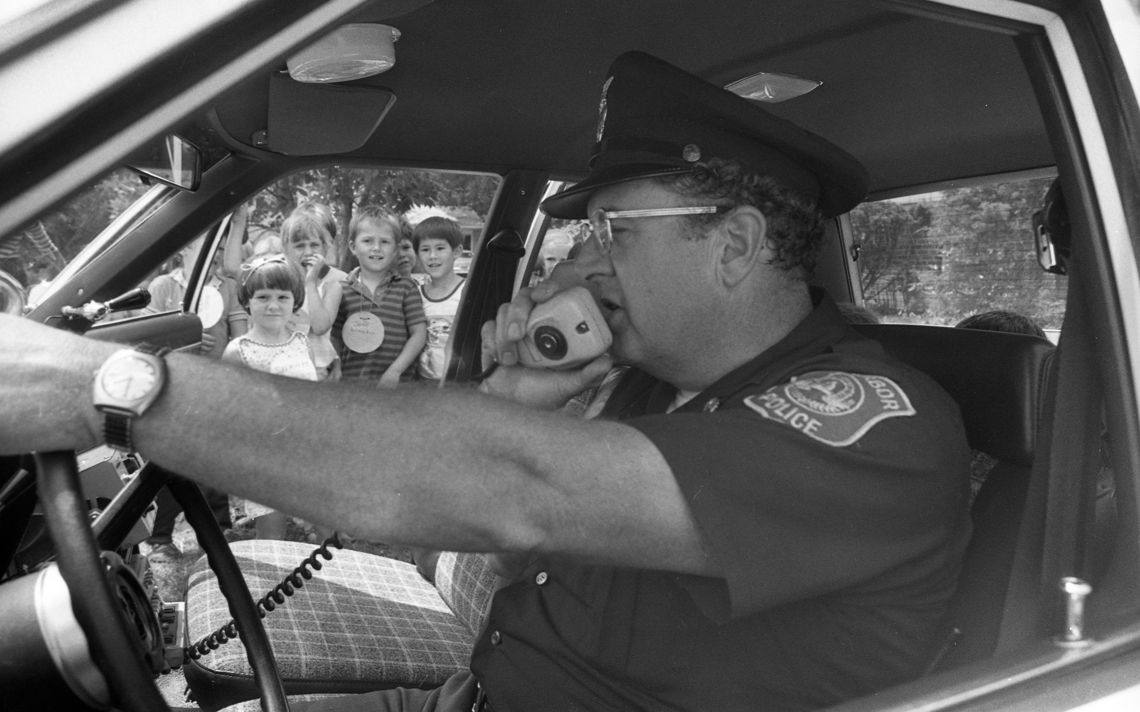 Ann Arbor Police Patrolman Patrick Nolan Demonstrates Loudspeaker at Safety Town, July 1982 image