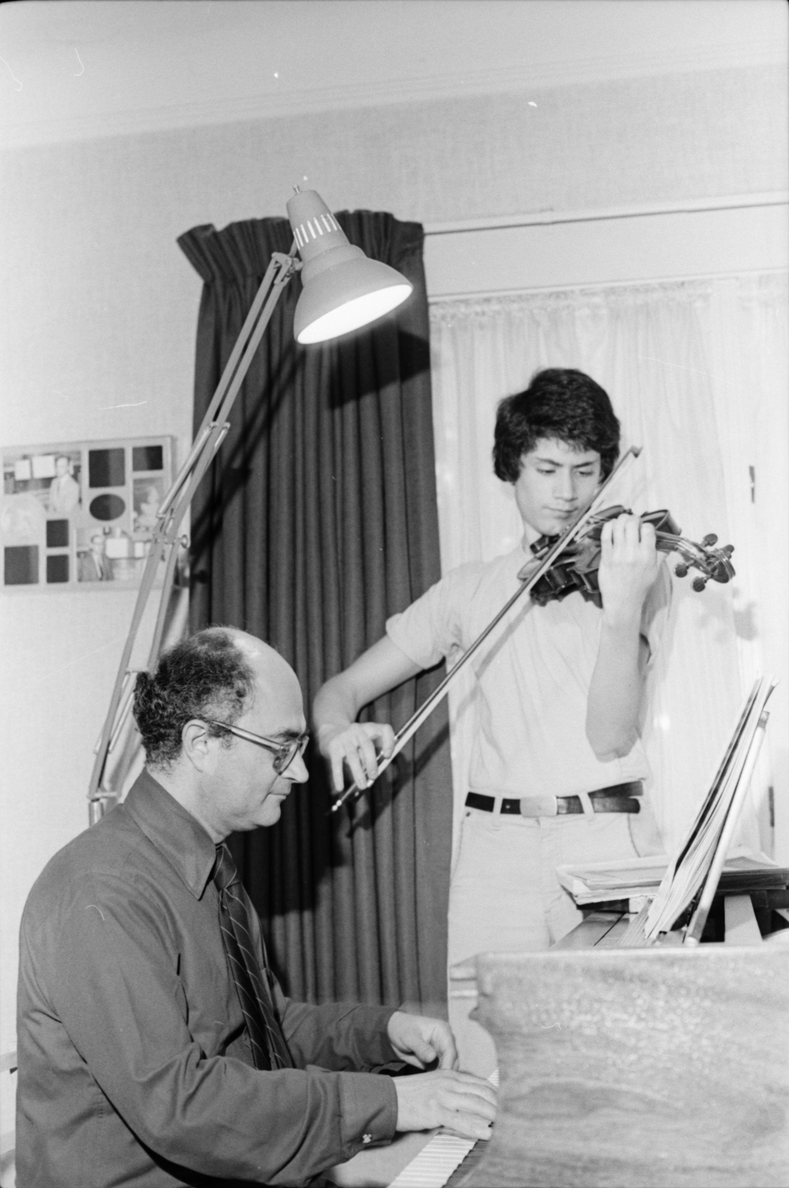 Community High Student Nuvi Mehta Takes a Violin Lesson From His Father, July 1980 image