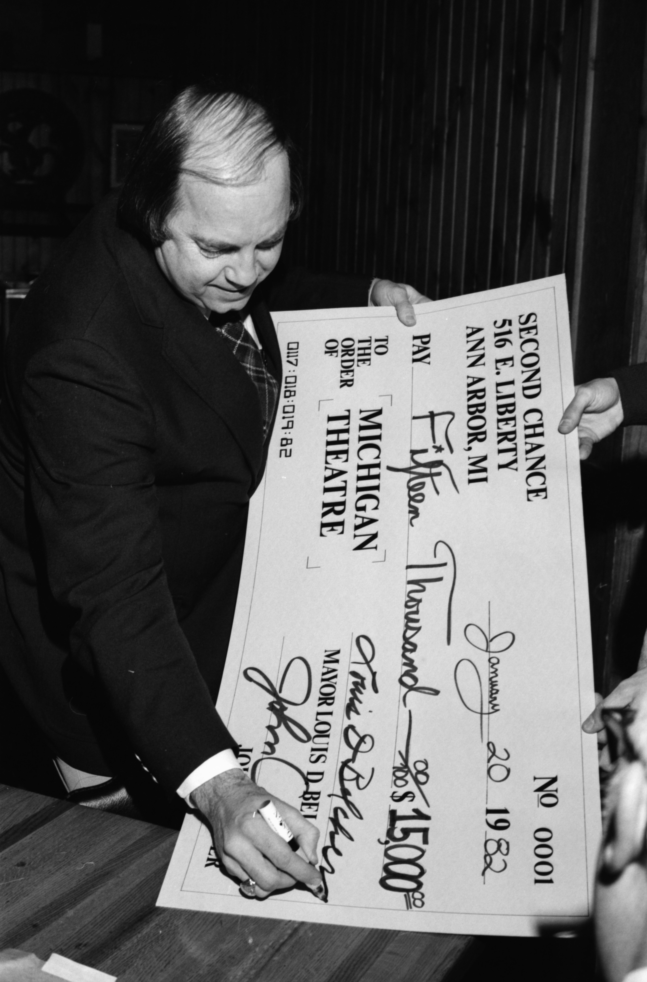Mayor Louis D. Belcher signs a giant check representing the $15,000 raised during the Las Vegas Millionaire's Party benefit for the Michigan Theatre, January 1982 image
