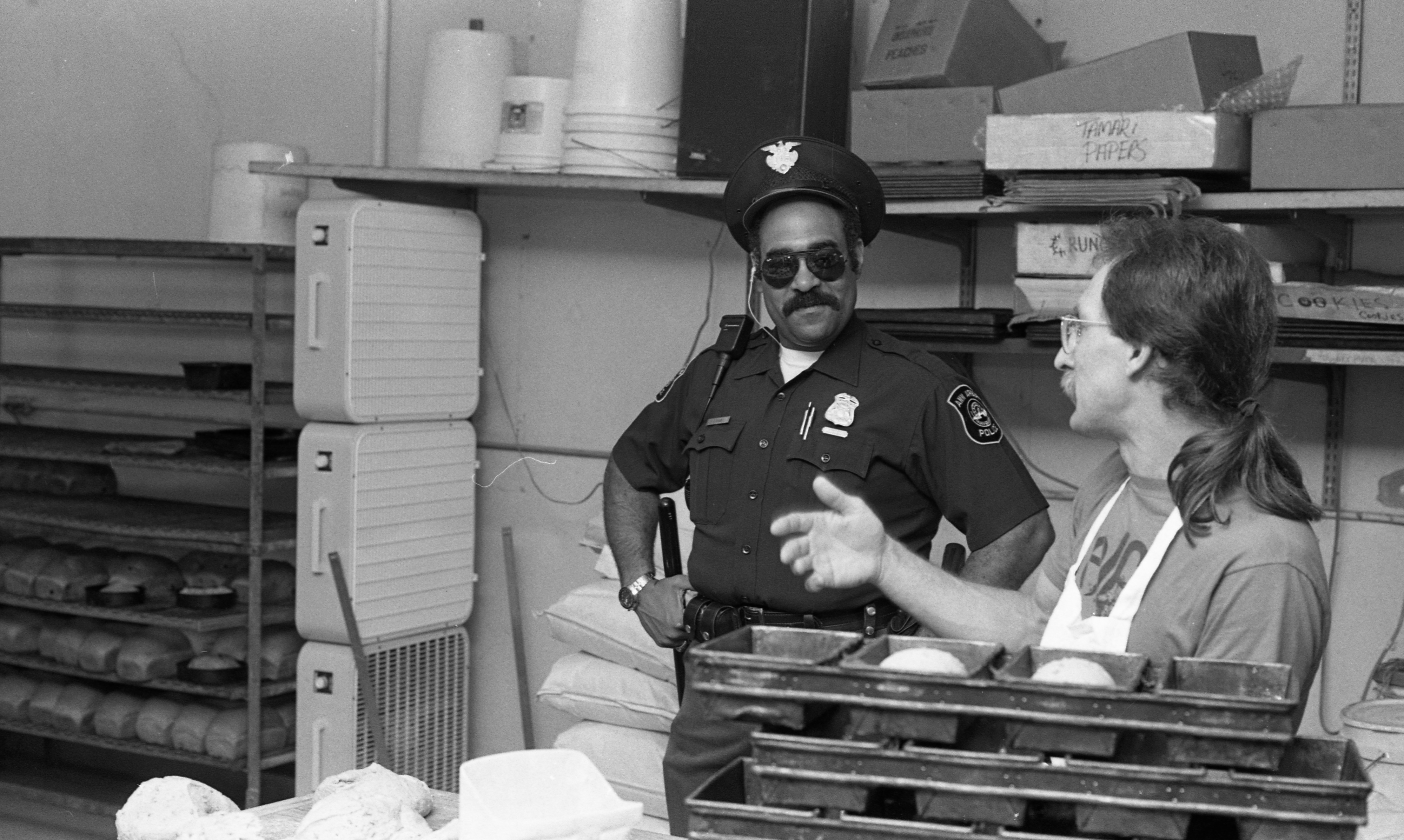 Ann Arbor Police Officer Richard Blake Talks With Tom Kenney of Wildflower Bakery, July 1988 image