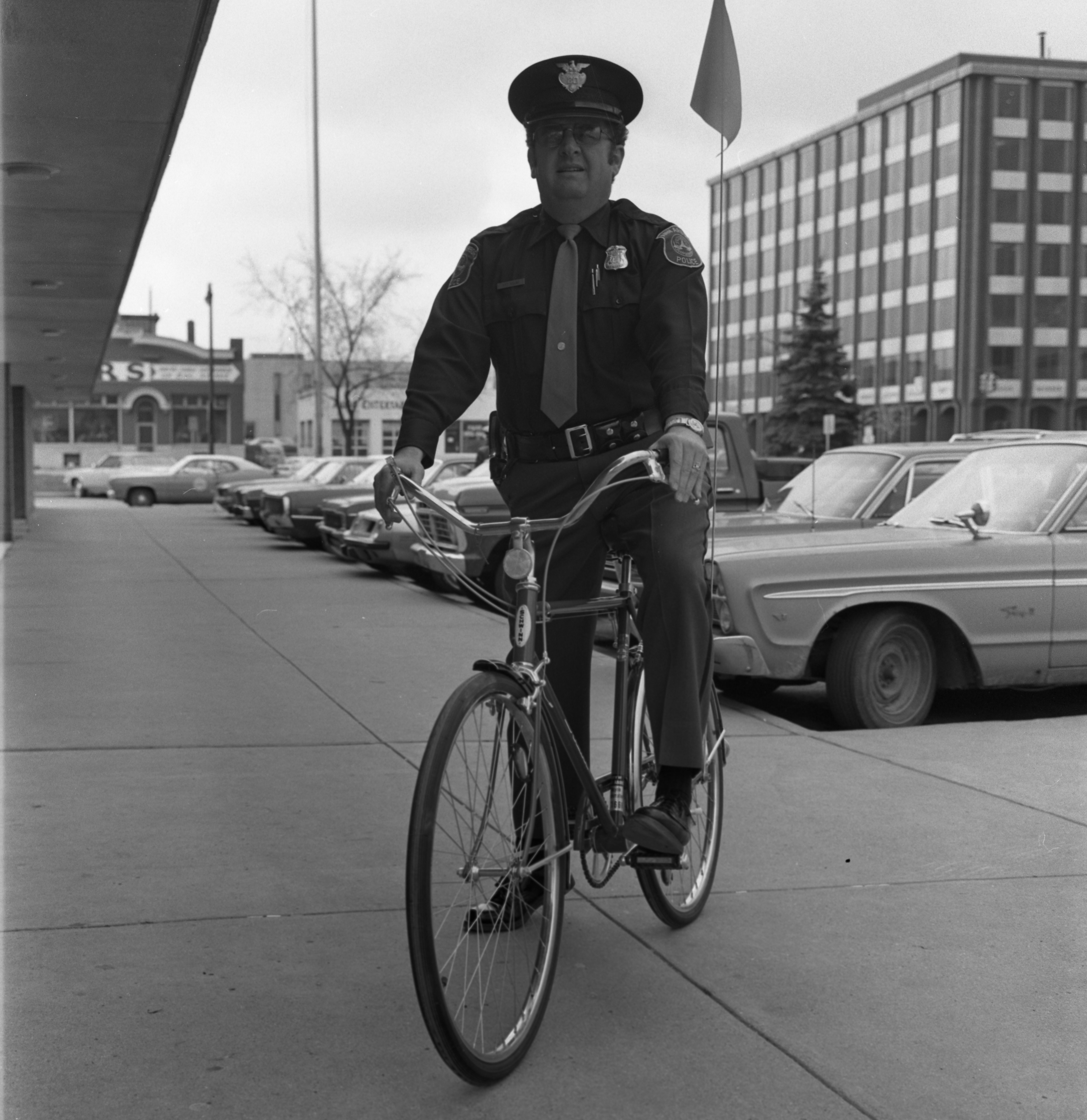 Ann Arbor Police Officer Pat Nolan On Bike Outside City Hall, May 1975 image