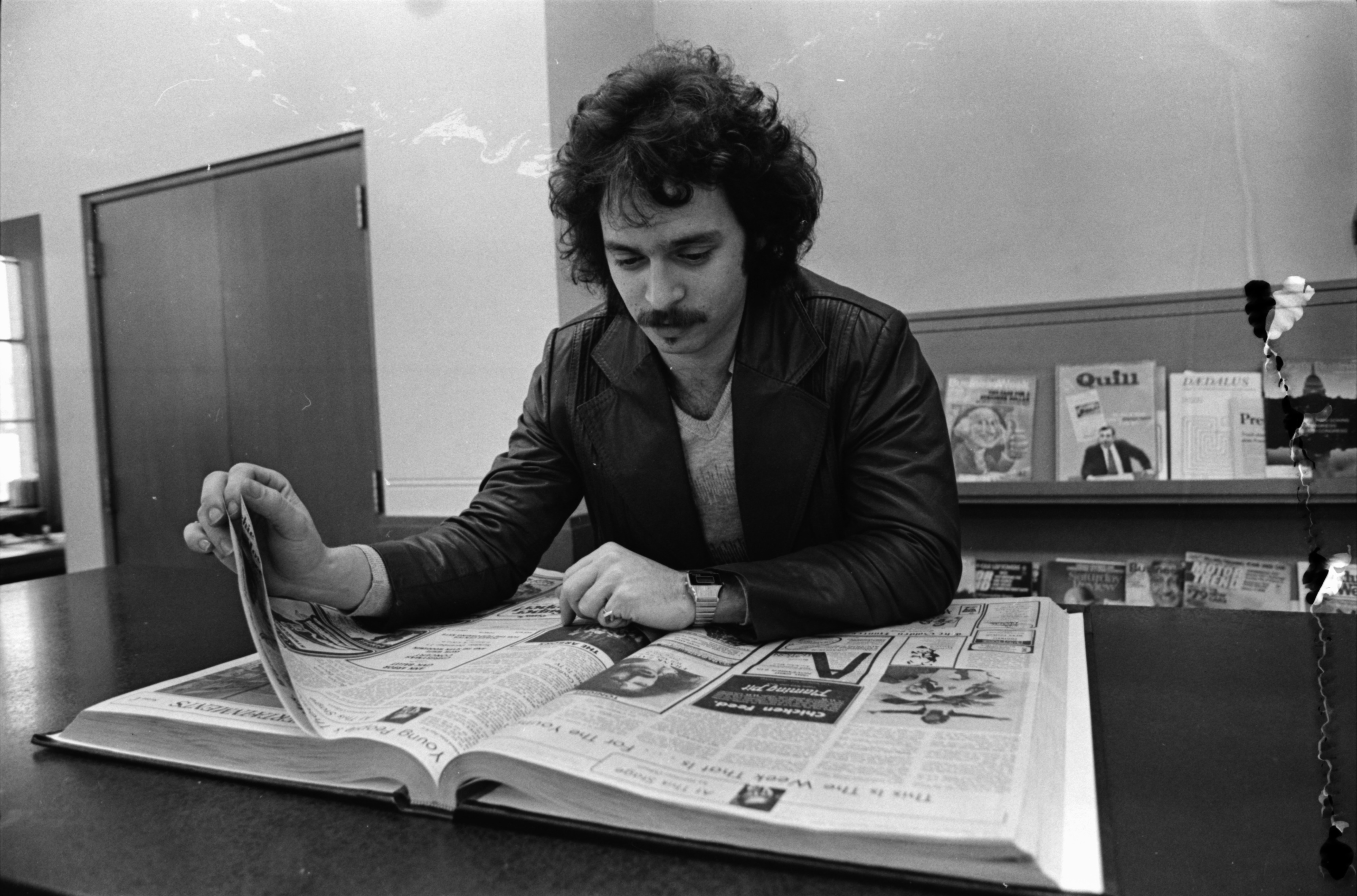 Wayne Kramer, formerly of the MC-5, looks through past editions of the Ann Arbor News, December 1978 image