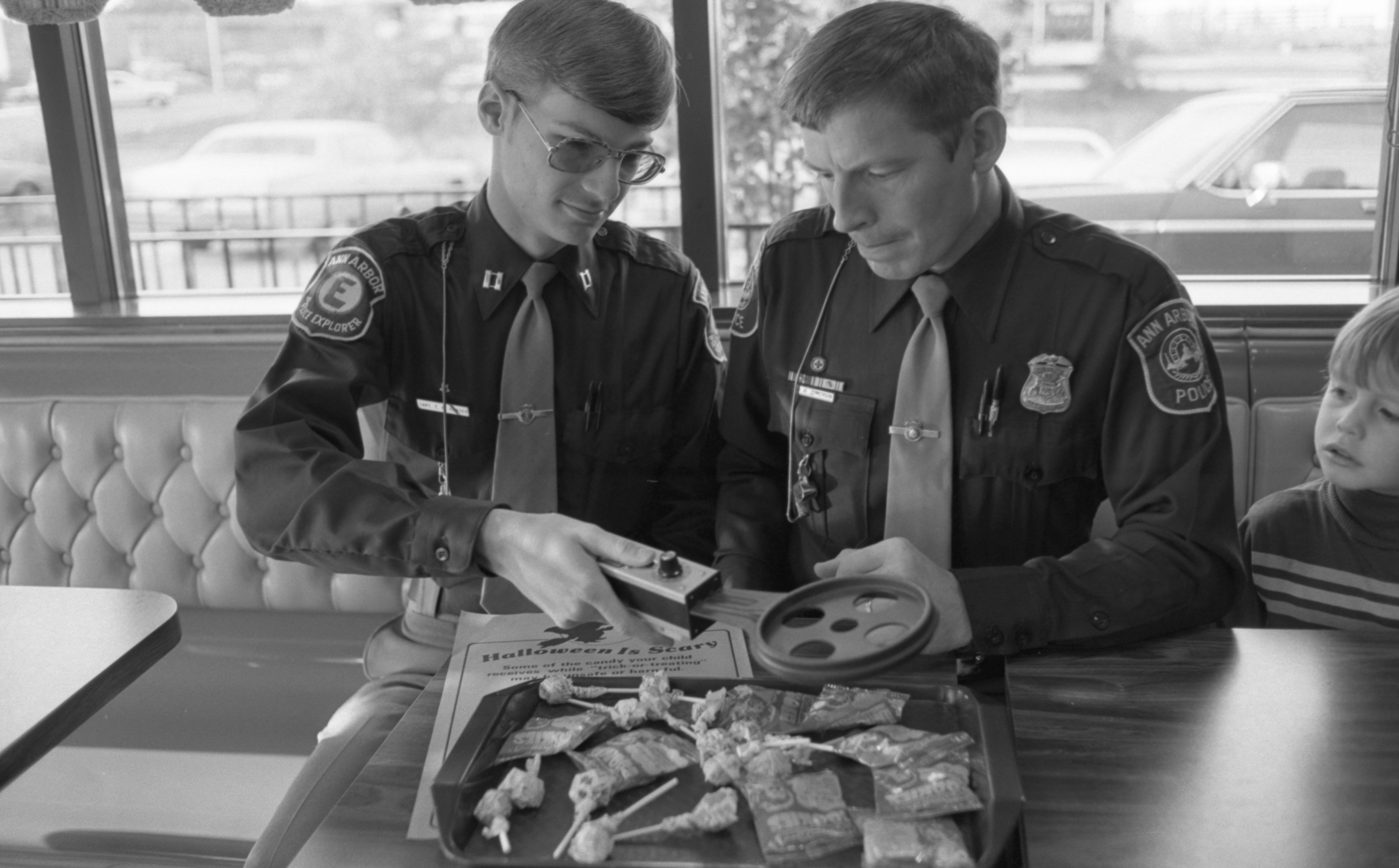 Todd Hansen, Explorer Scout, & Harry Jinkerson, Ann Arbor Police Officer, Test A Metal Detector On Halloween Candy, October 1981 image
