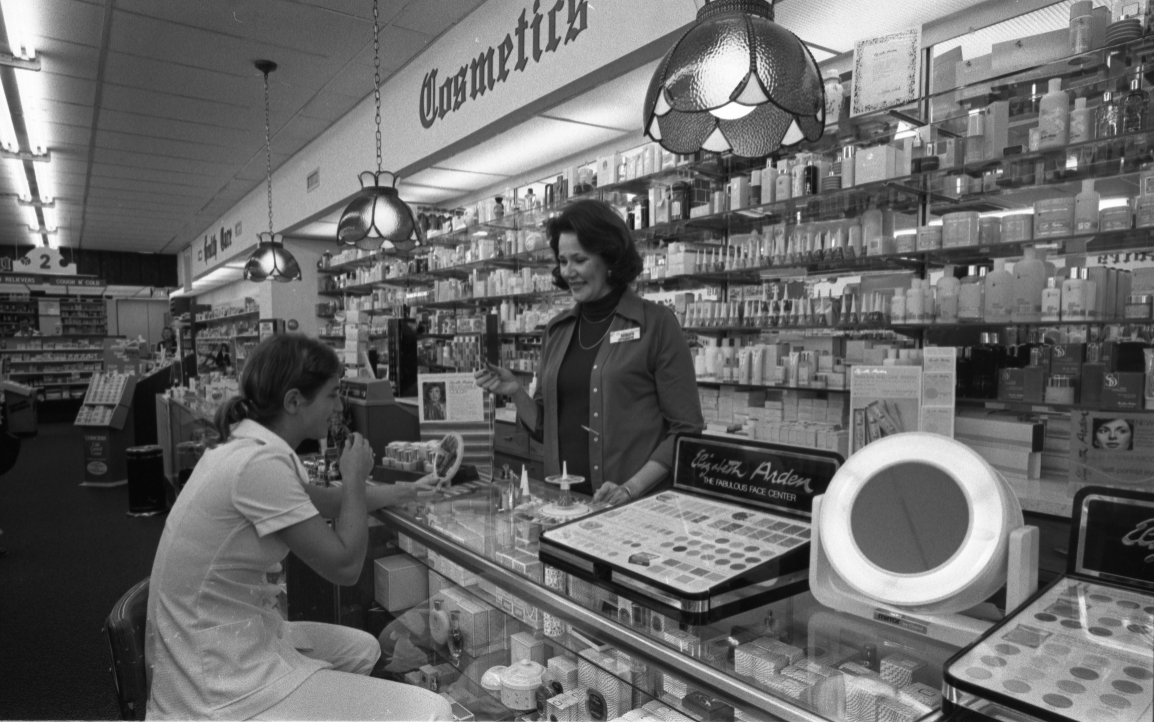 Trying On Makeup At The Cosmetics Counter Inside Richardson's Pharmacy, September 1975 image