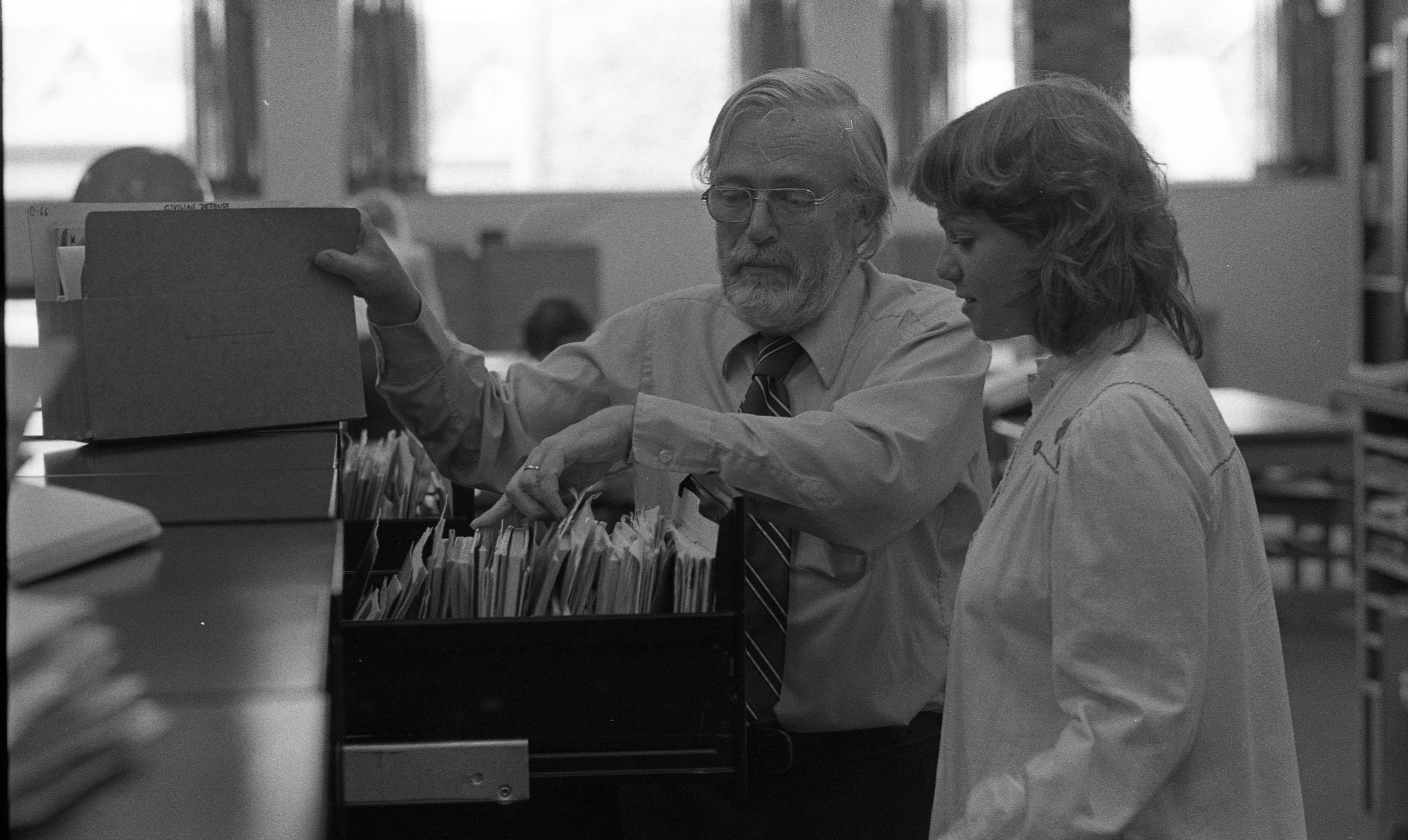 Ann Arbor Public Library Reference Librarian Gene Wilson Works With Patron on Research, July 1976 image