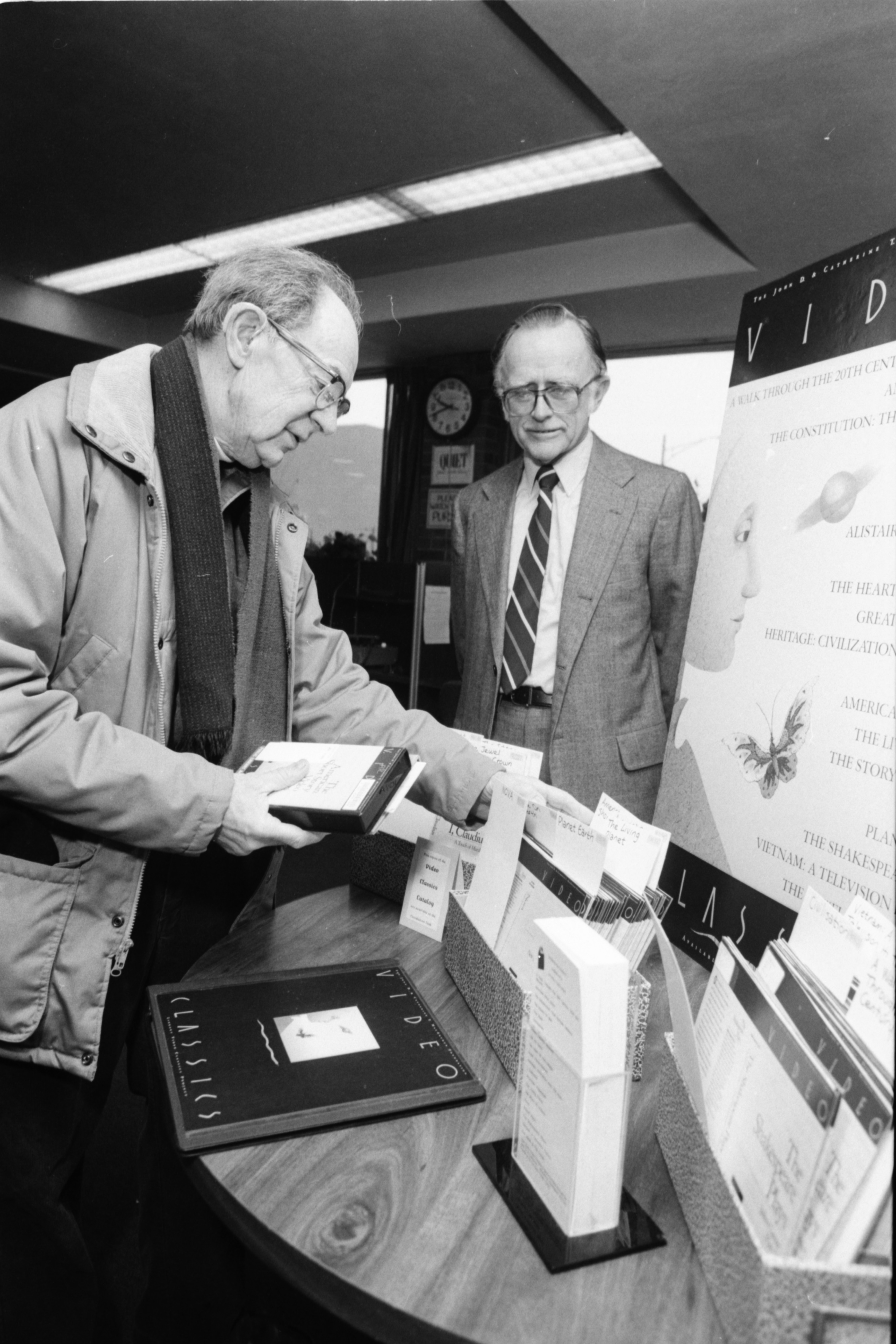 Henry Meyer and Don Axon of the Friends of the Ann Arbor Public Library Look Over New VHS Collection at the Library, January 1989 image