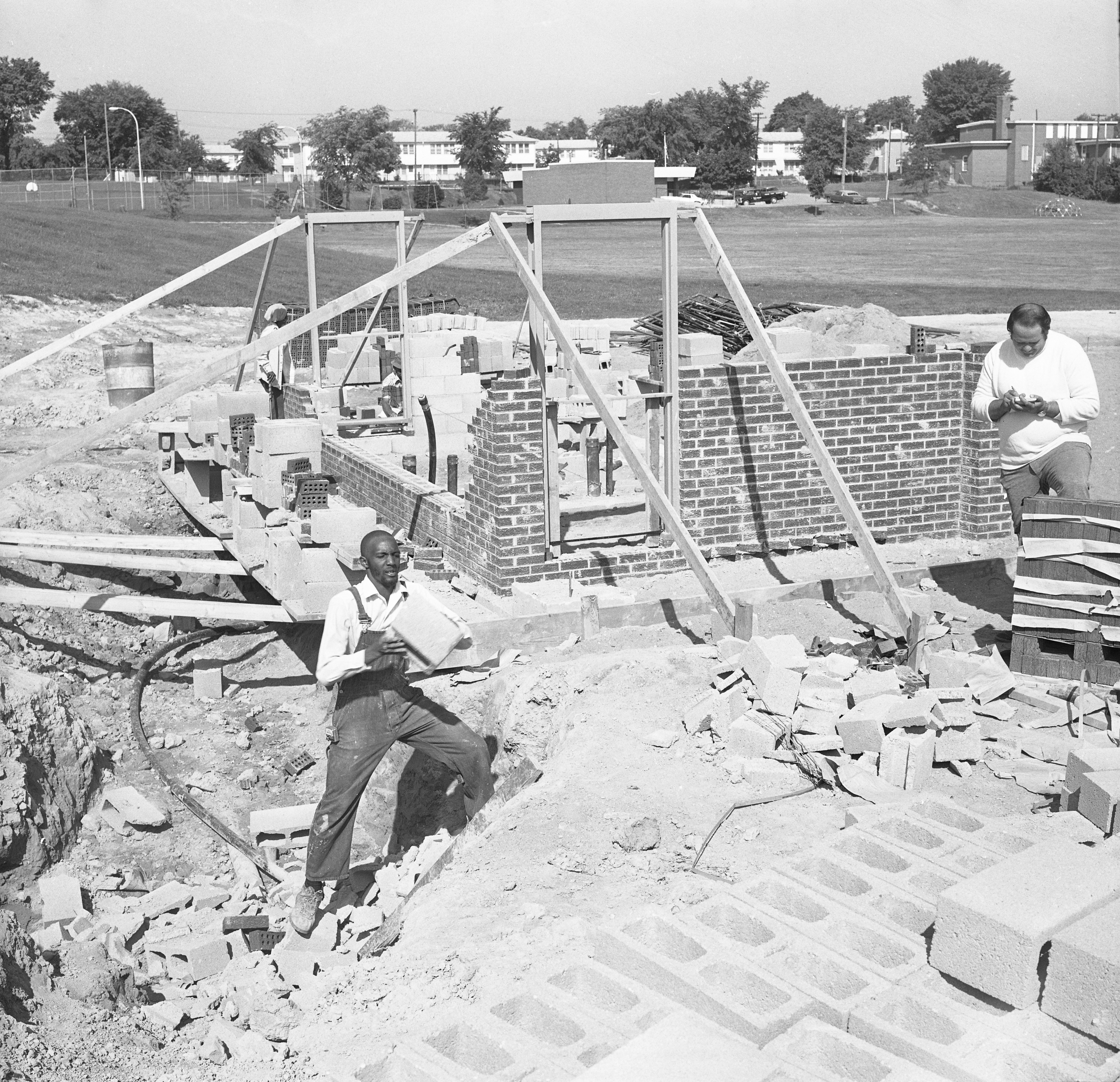 Man Picks Up Cement Blocks At Vandalized Parkridge Project, June 10, 1975 image