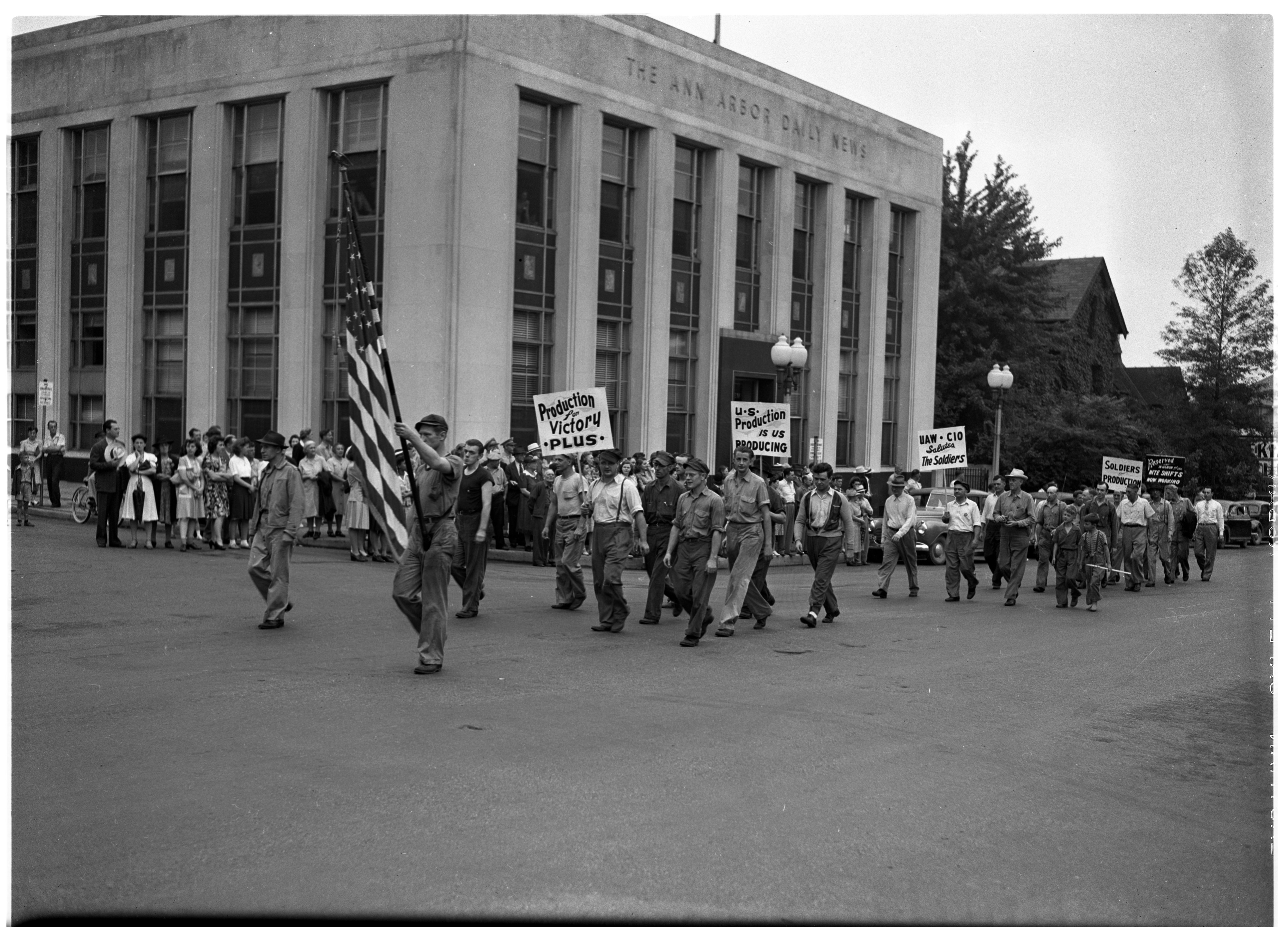 Local plant workers parade past Ann Arbor News building in the U.S. Army Honors Labor, Industry & Agriculture: Parade, August 1943 image