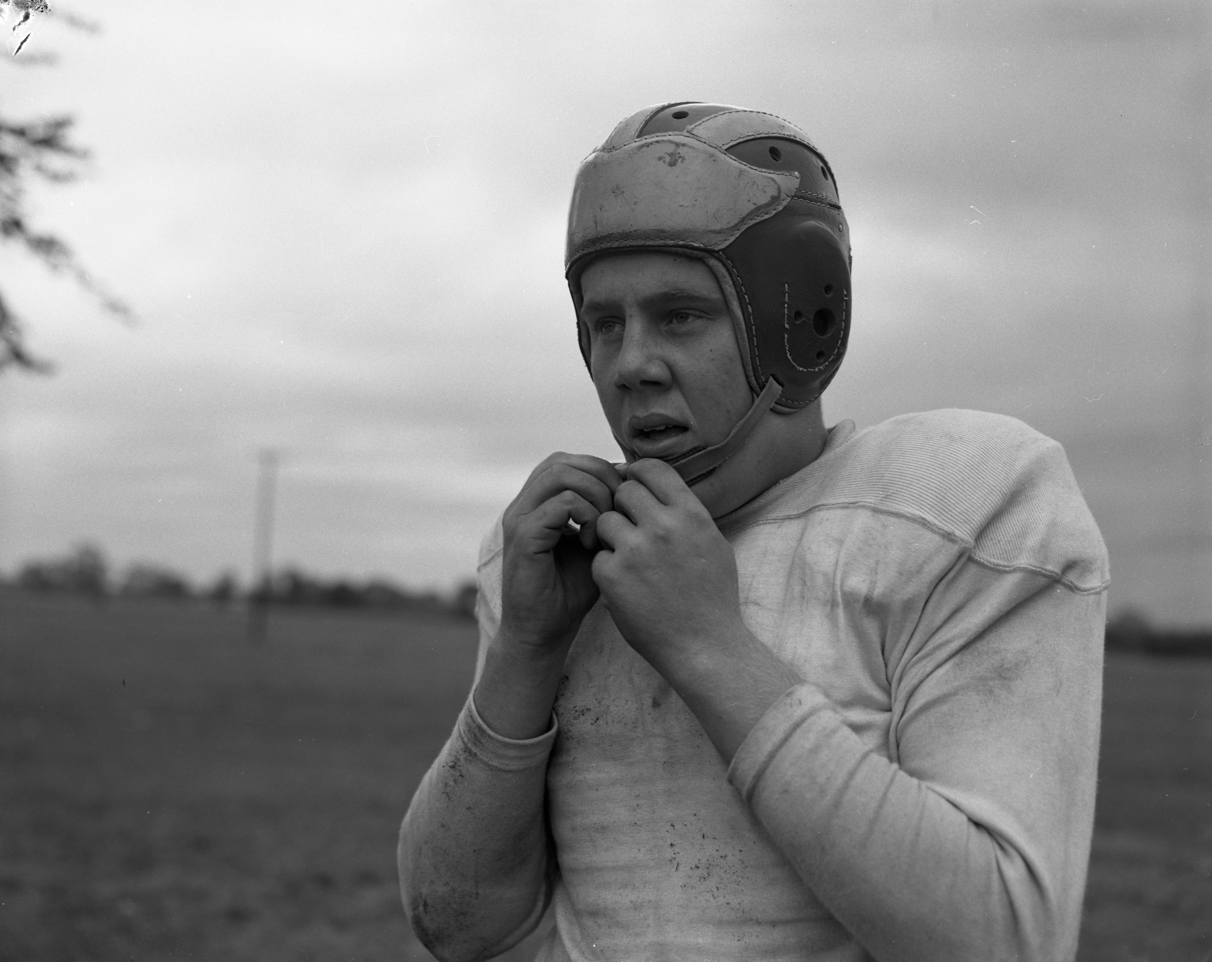 Bob West puts on a U-M maize and blue helmet at Willow Run High, September 1954 image